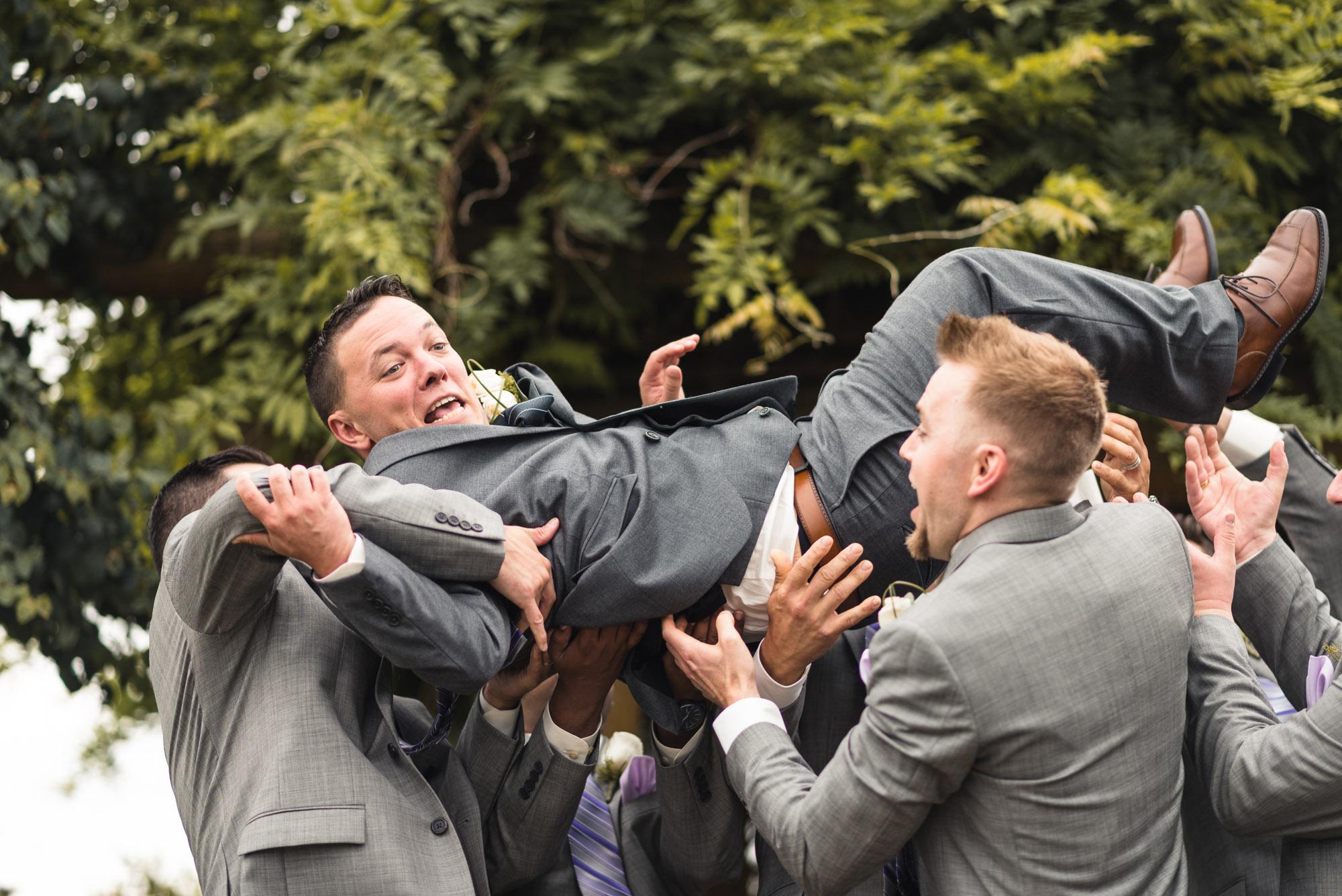 Groomsmen tossing Groom into air