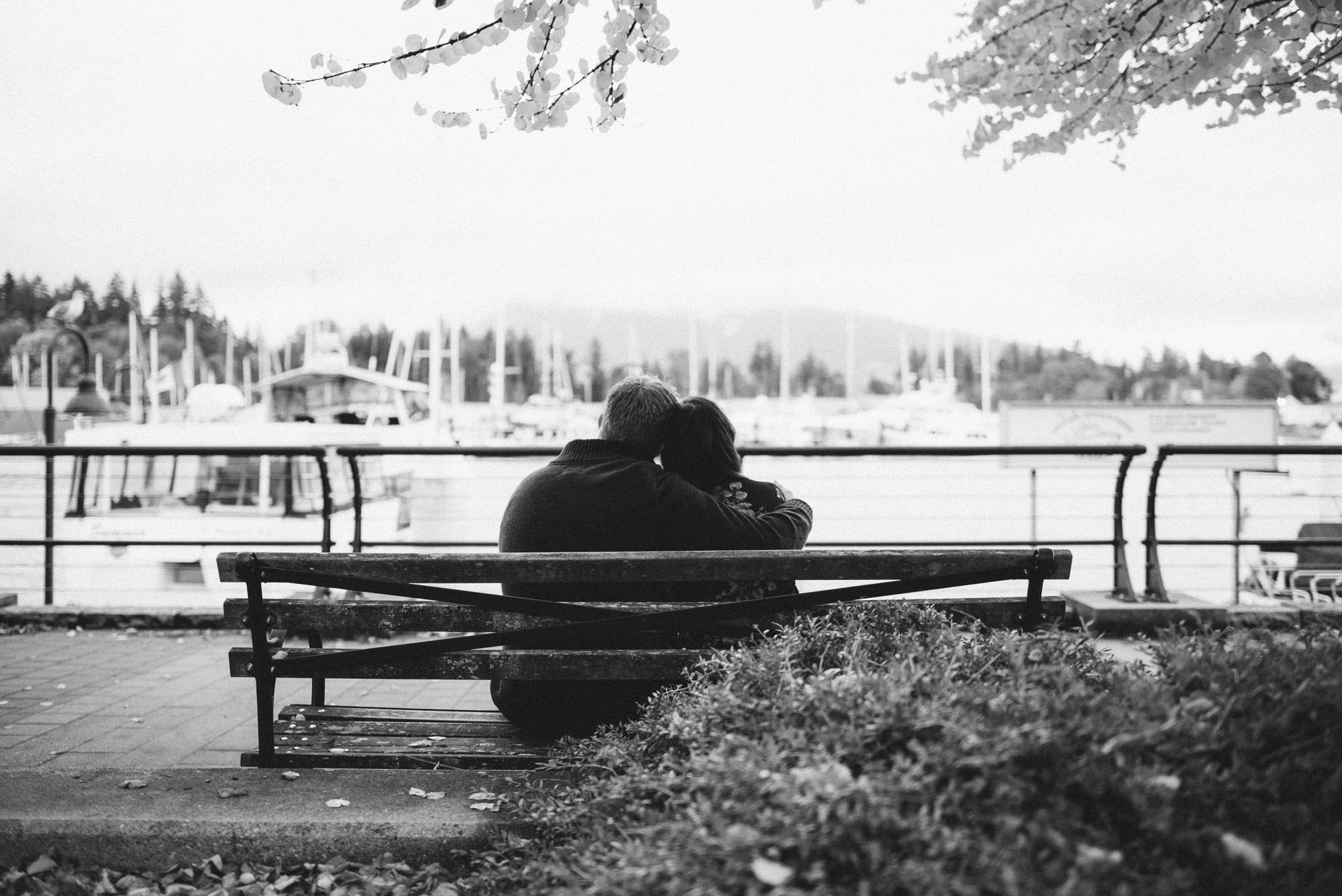 Couple hugs on park bench