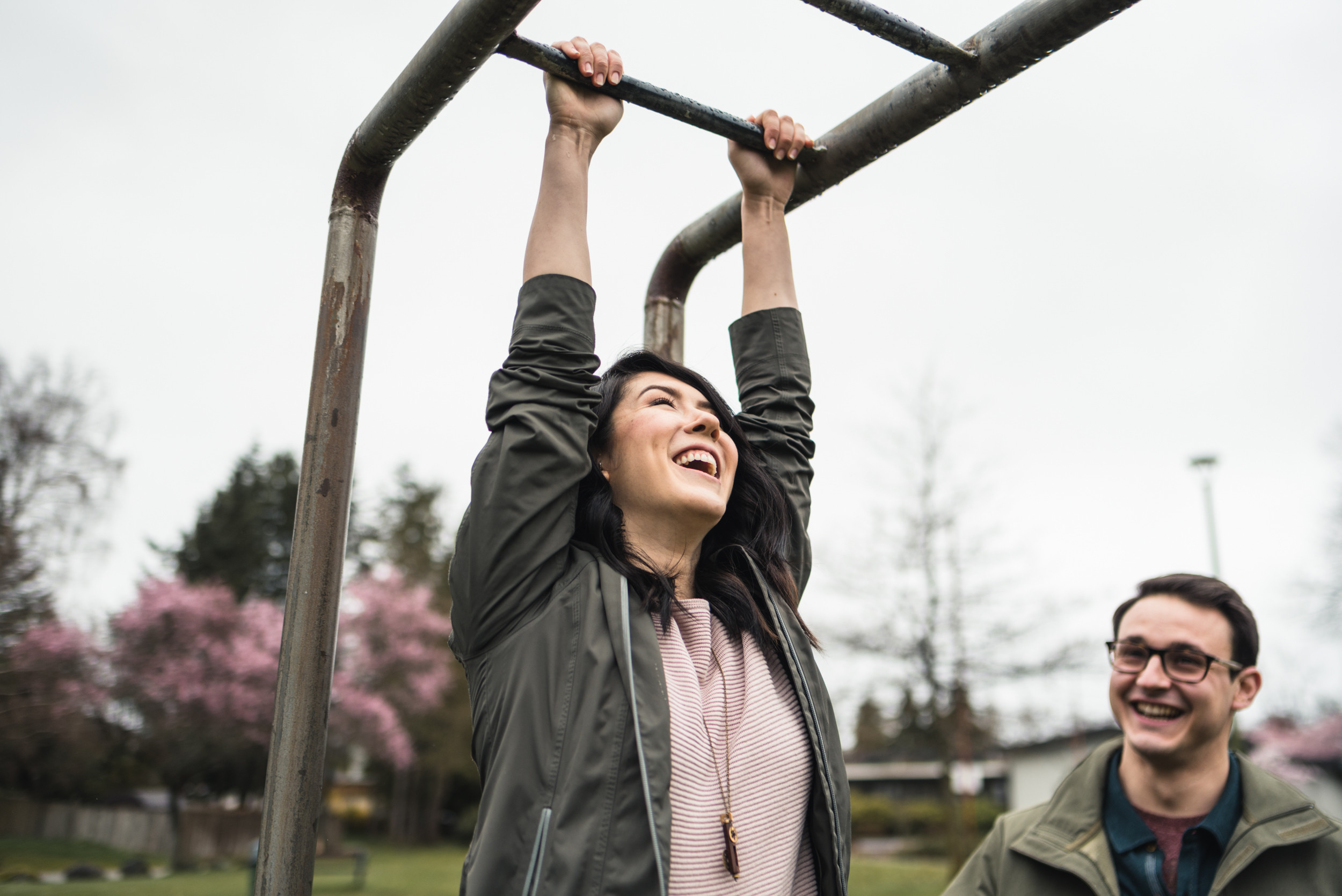 Couple swinging on bars at playground