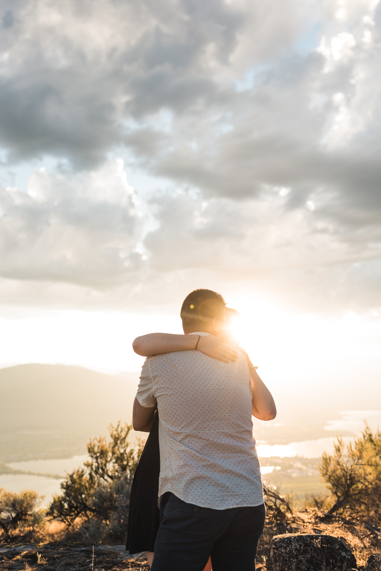 Engaged couple embraces with sunset on Anarchist Mountain, Osoyoos