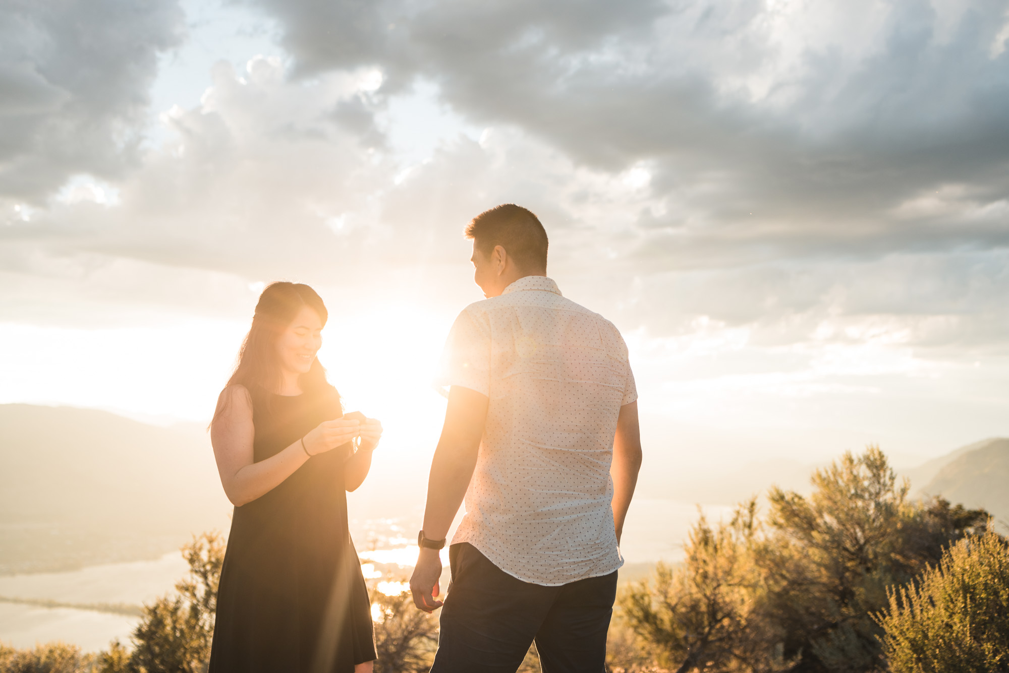 Engaged couple looks at ring with sunset on Anarchist Mountain, Osoyoos