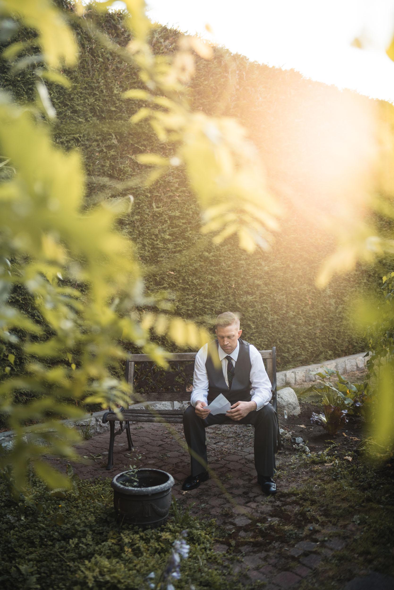 Groom holding letter in garden