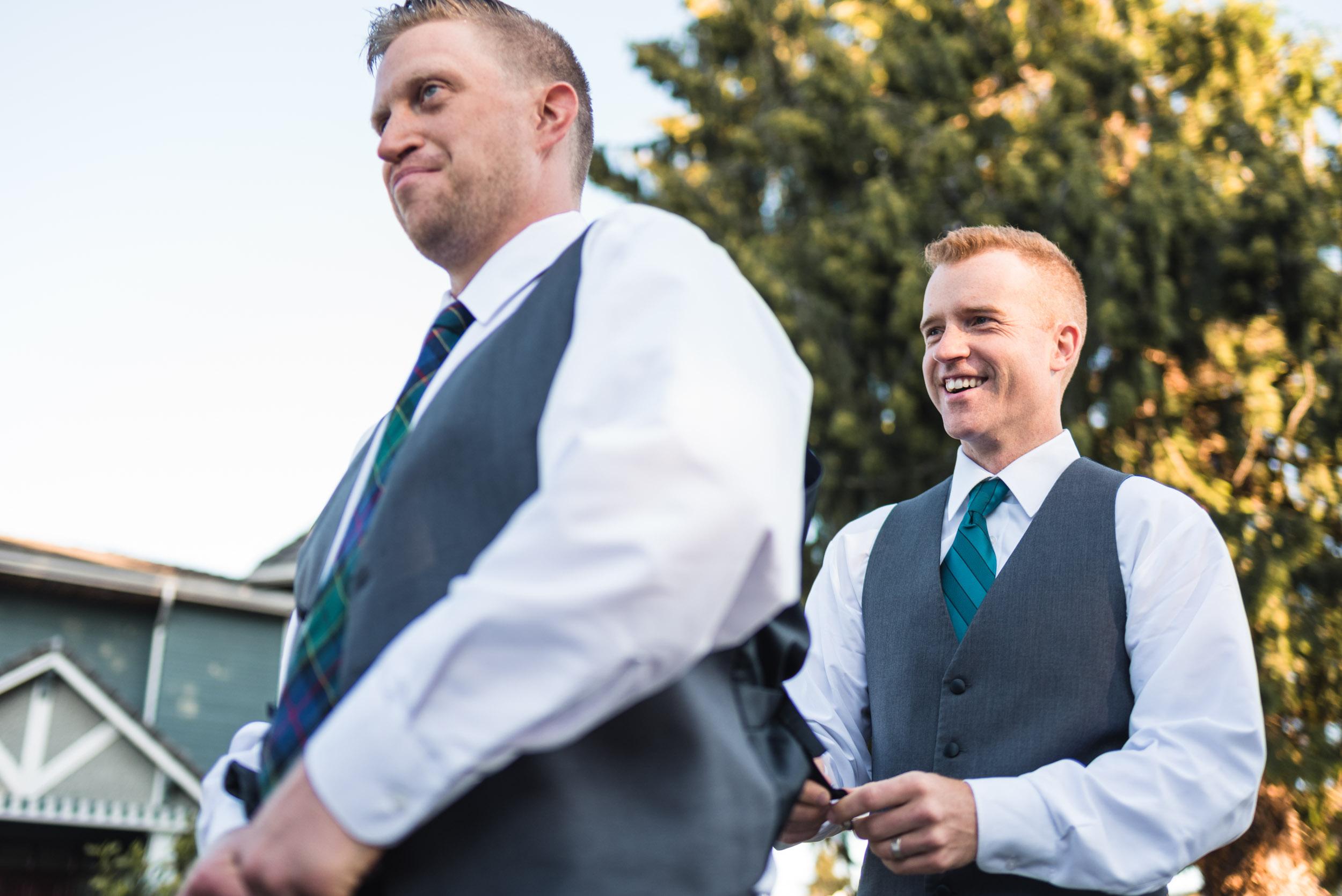 Groomsman helping groom get dressed