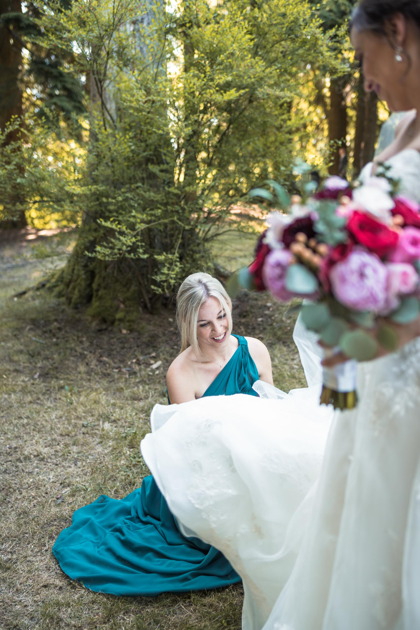 Bride helped with dress by Bridesmaid