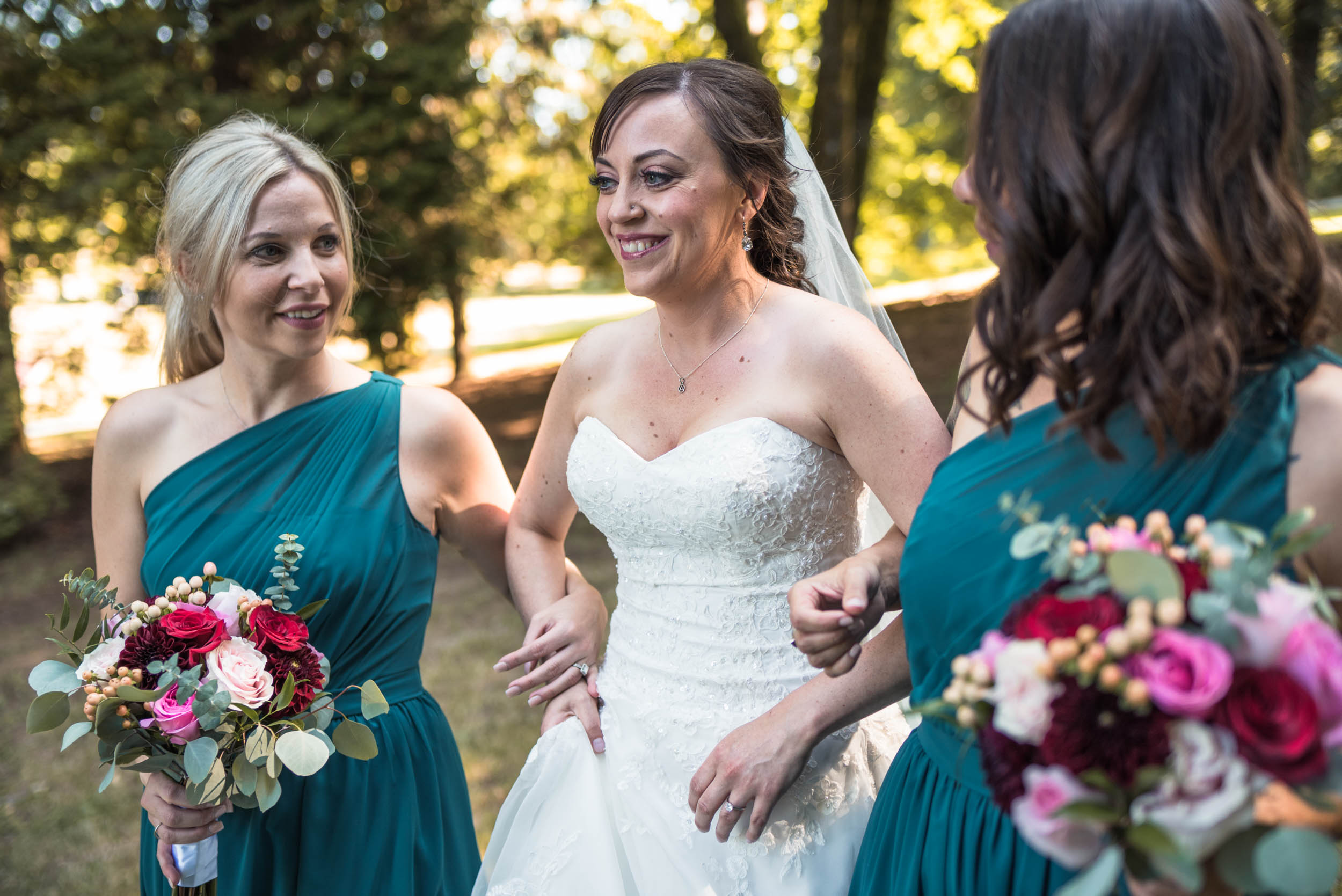 Bride and bridesmaids walk through forest