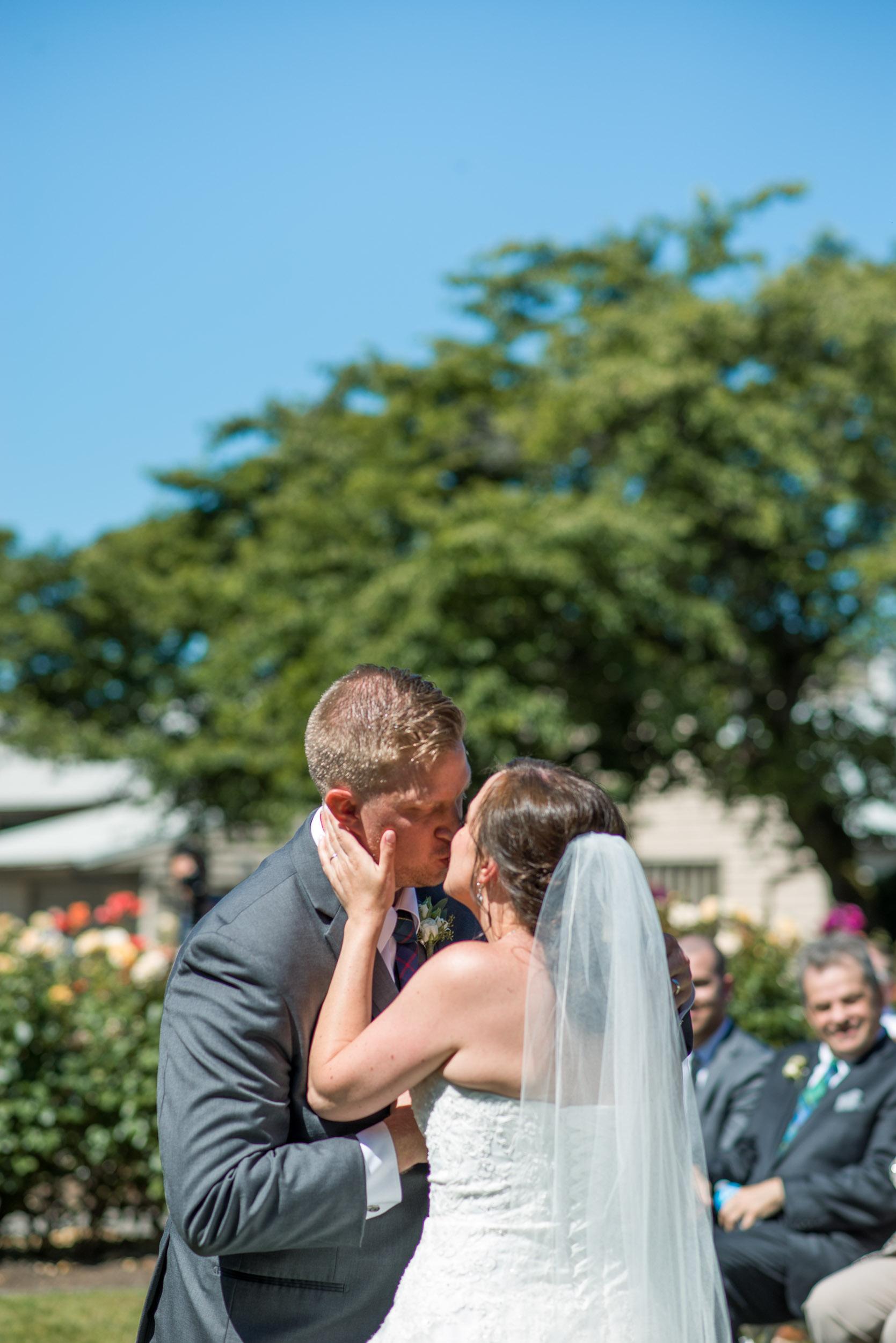 Wedding ceremony in rose garden first kiss