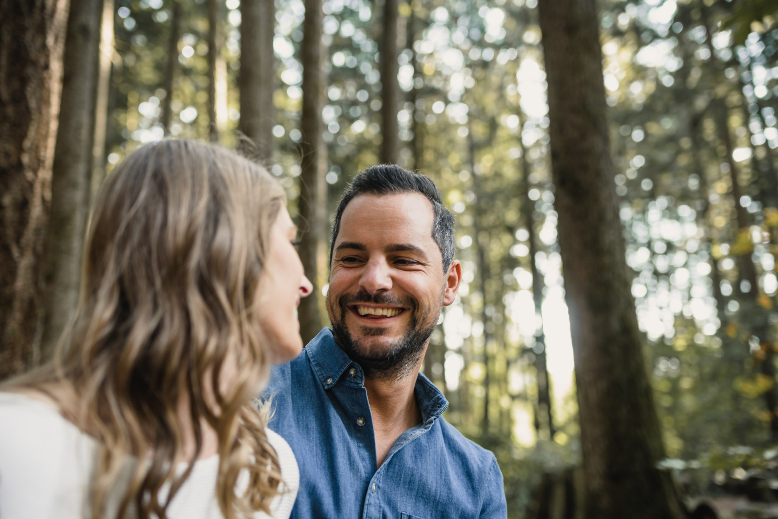 Couple hanging out in forest looking at each other