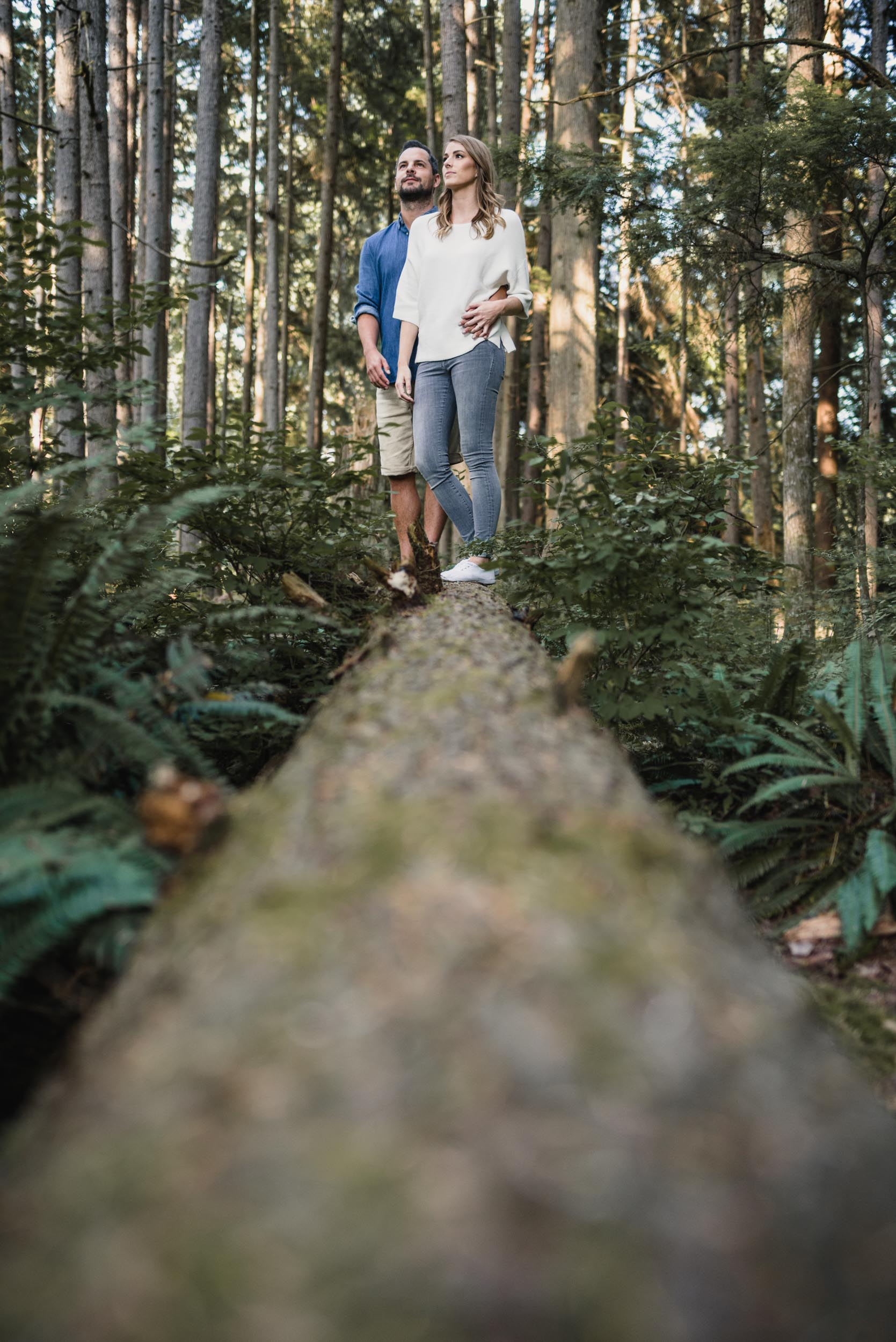 Couple stands together on fallen tree in forest