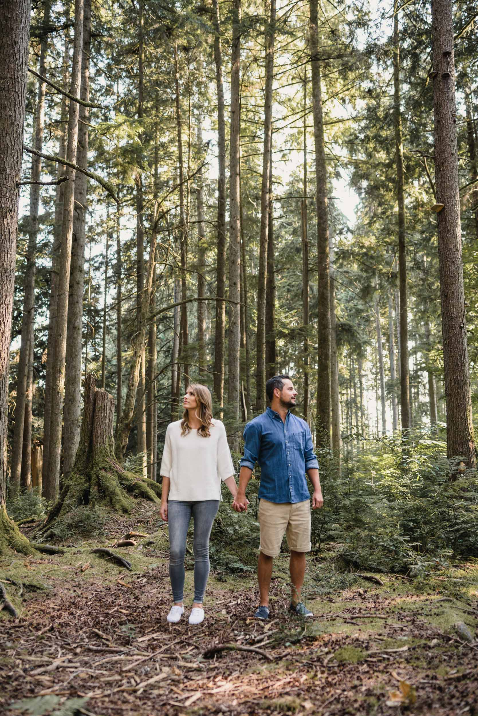 Couple posing with tall trees in the forest