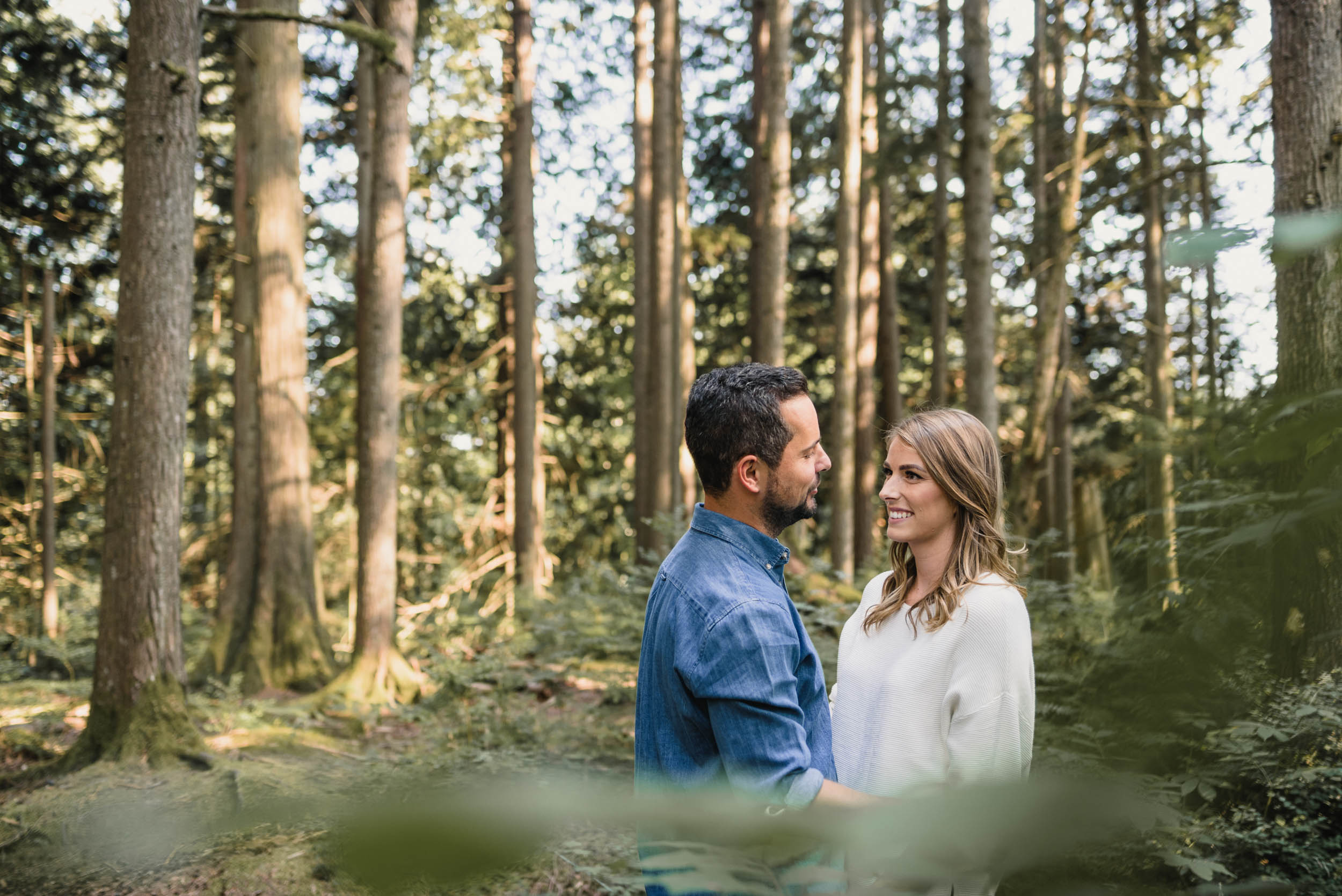 Couple smiling together in forest foliage
