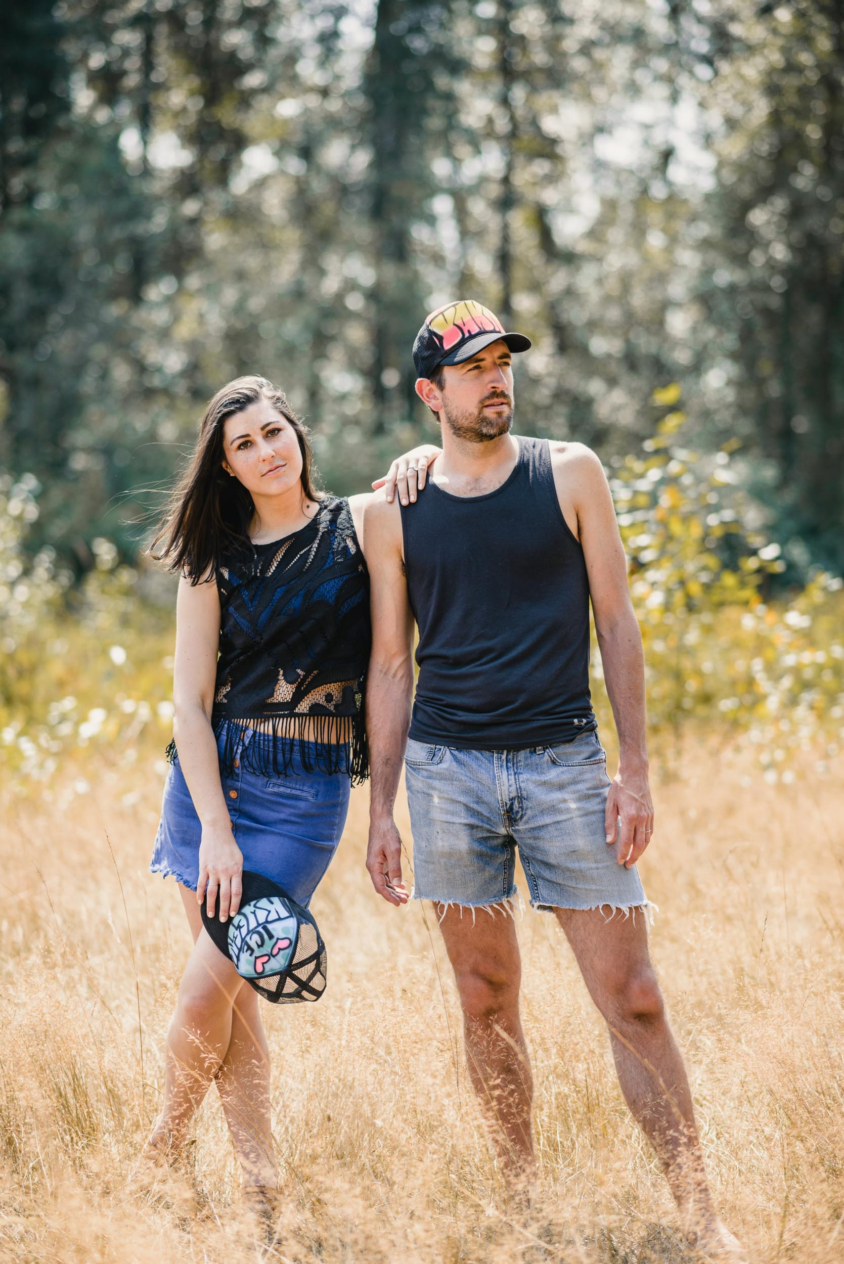 Couple standing together in tall grass field