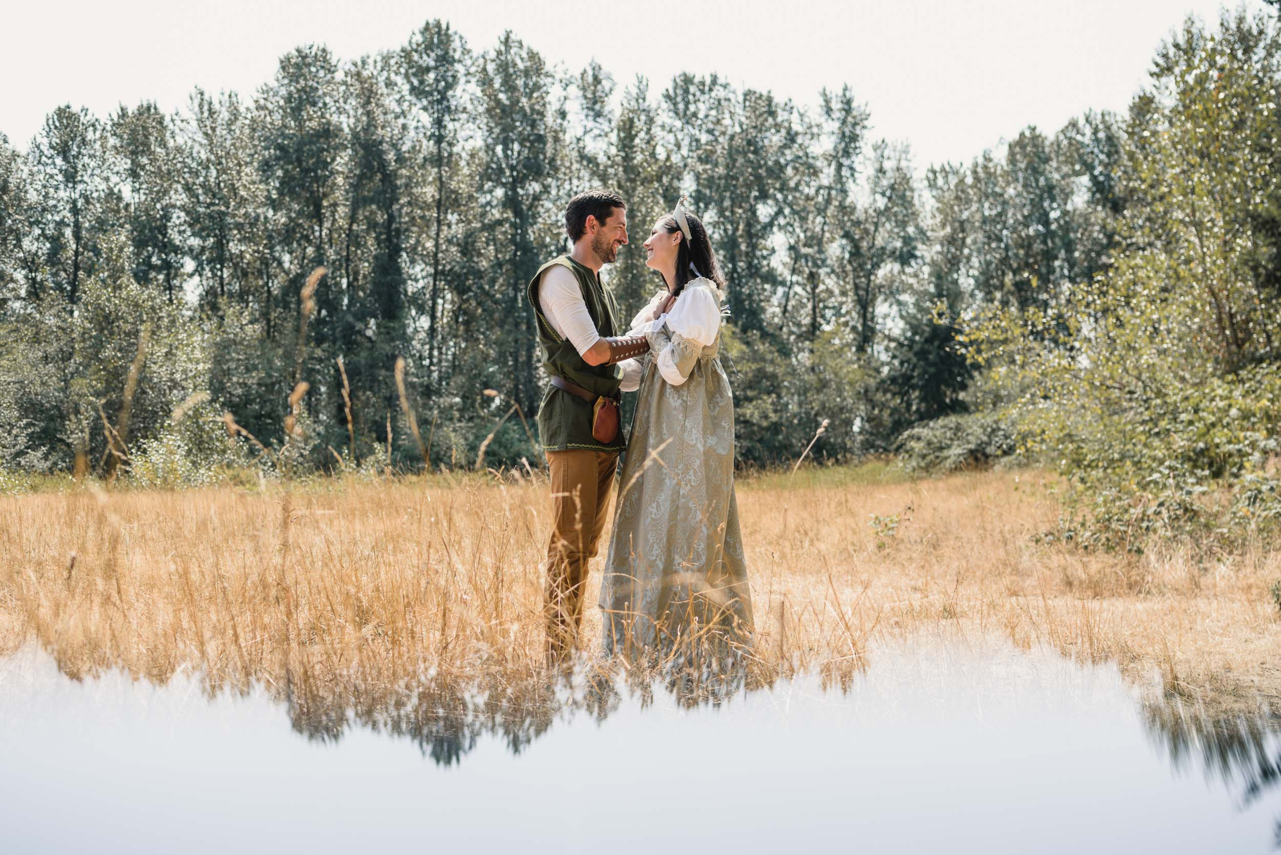Couple facing each other in field with medieval costumes