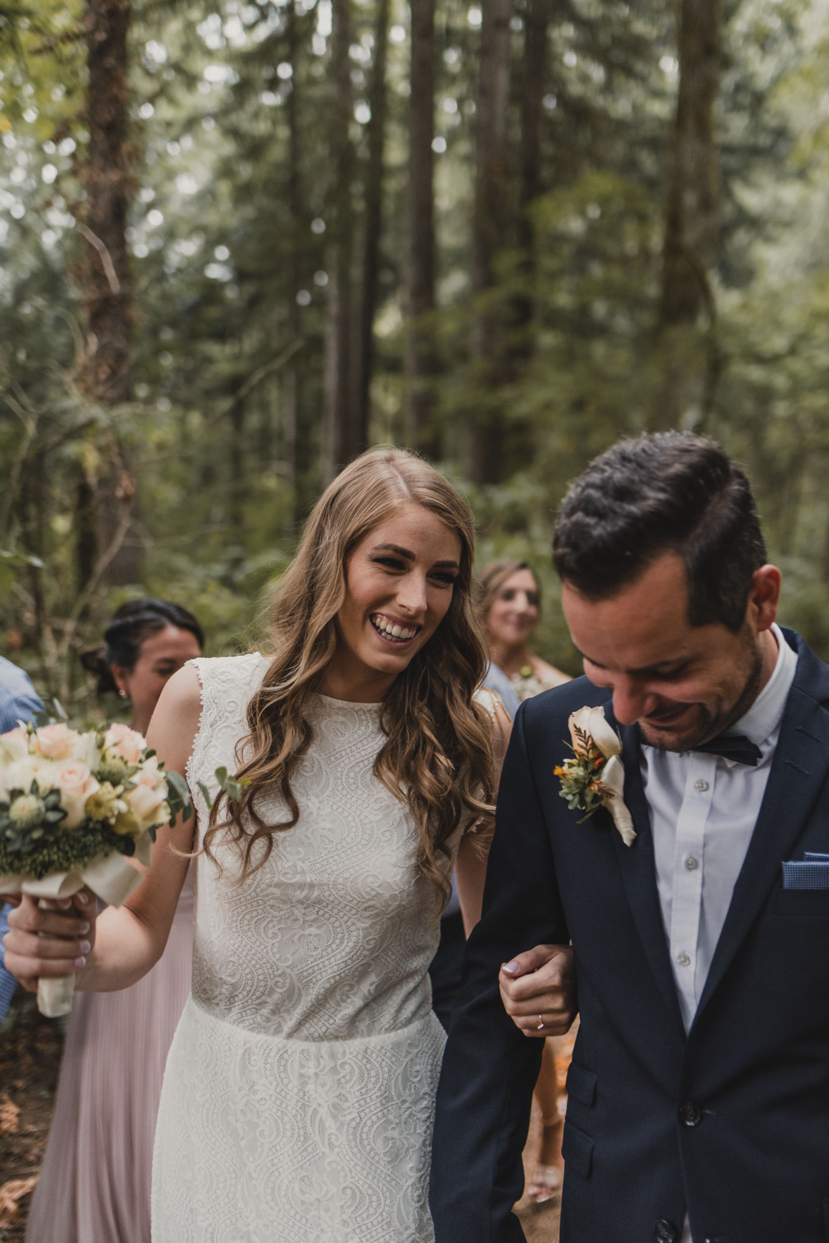 Bride and groom walk through forest