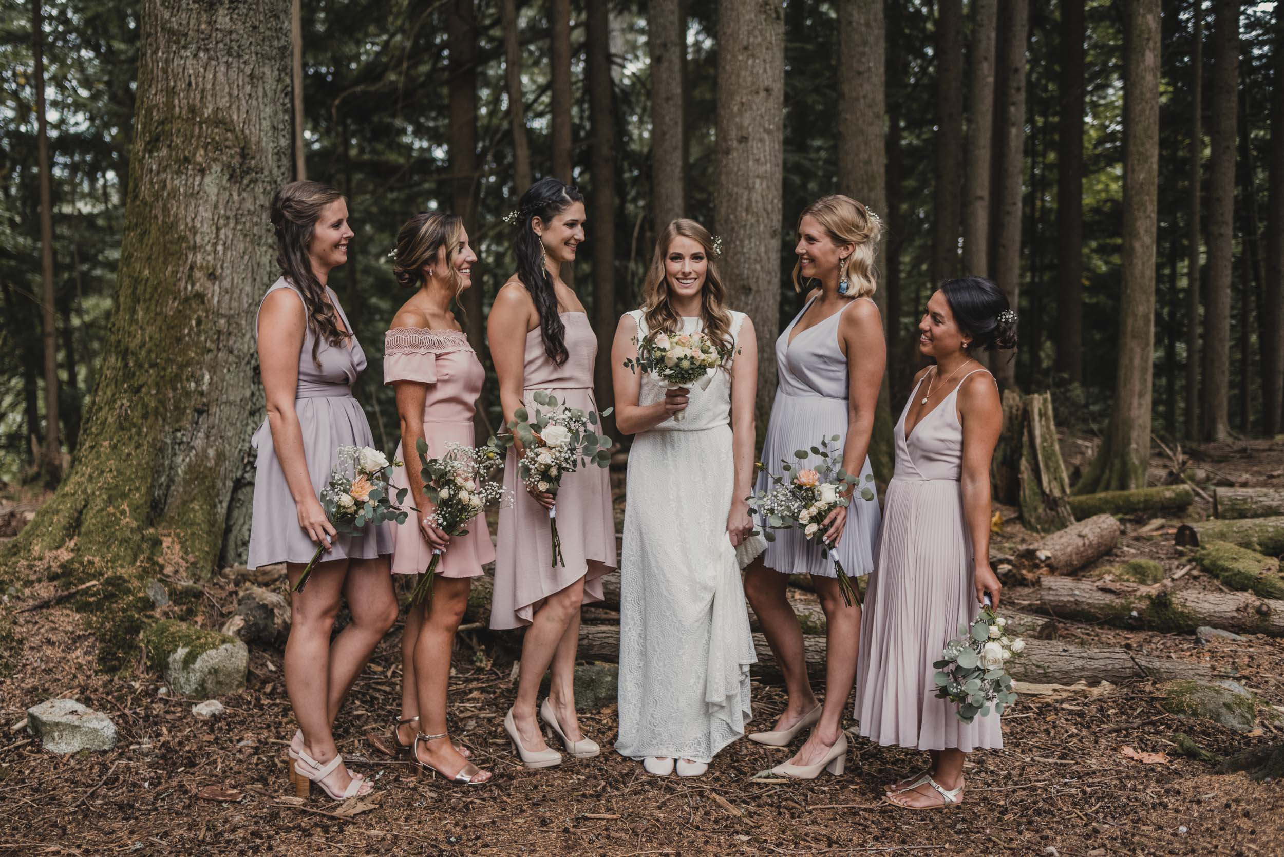 Bride and bridesmaids group photo in forest
