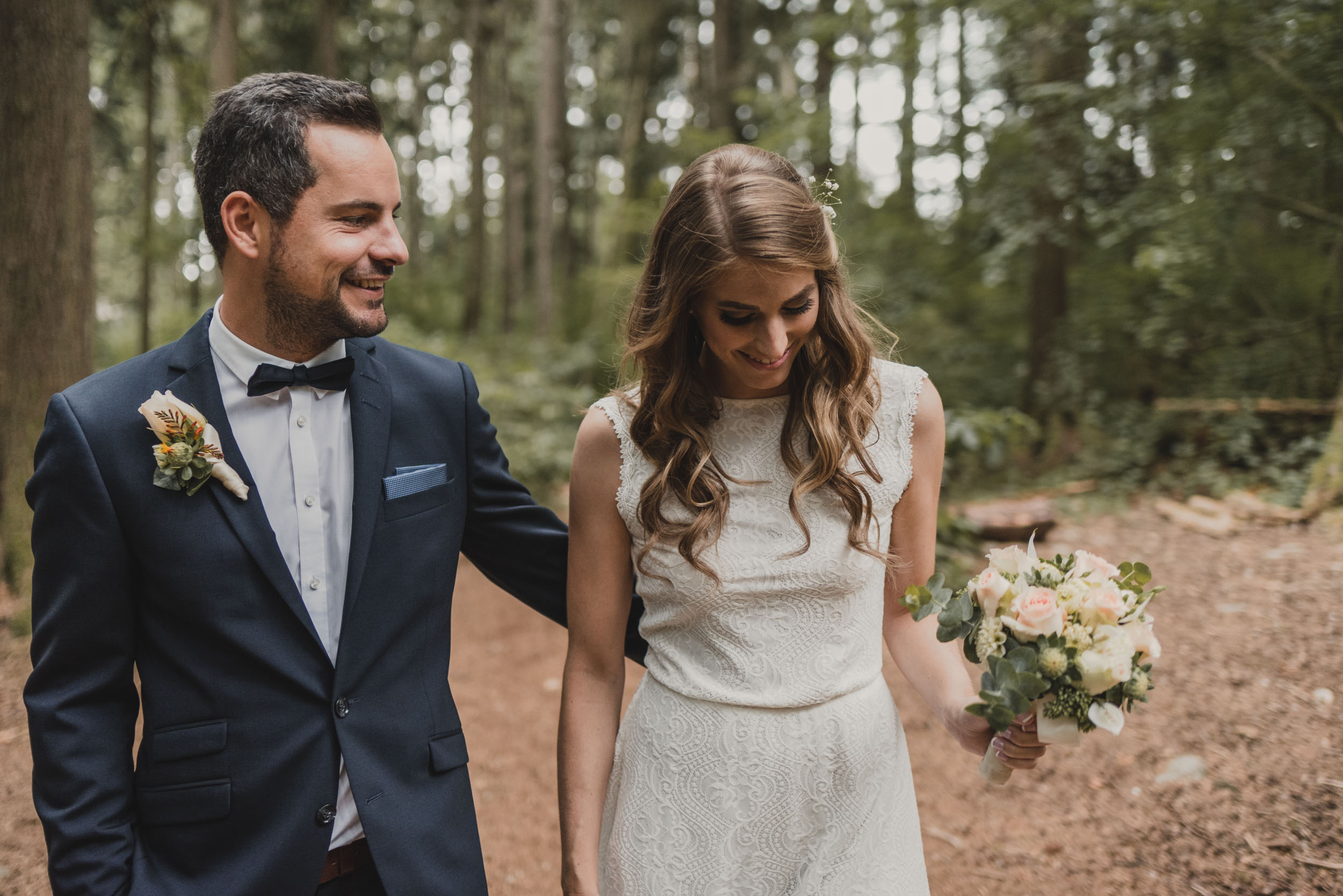 Bride and Groom walk through forest trail