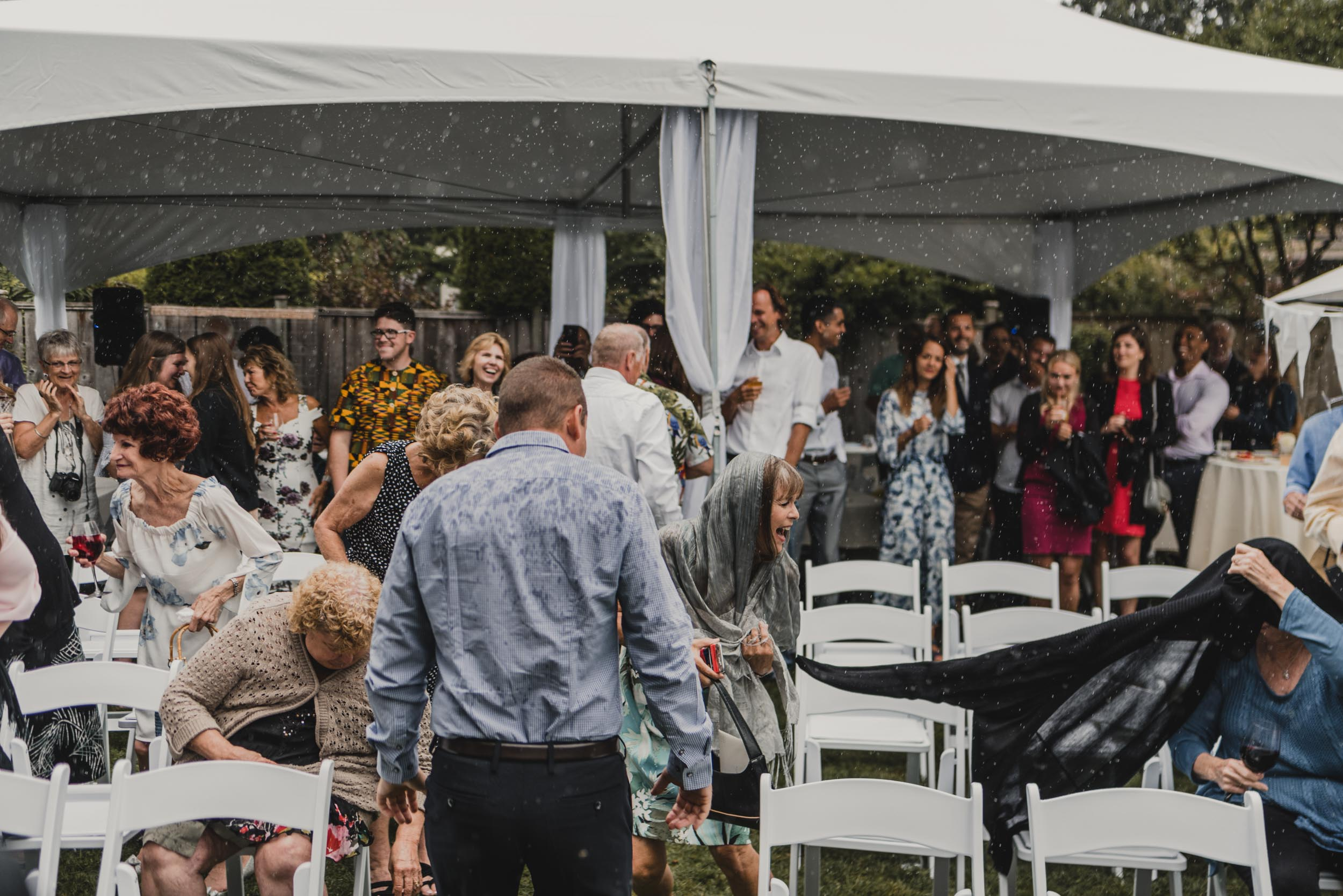 Wedding guests running from rain