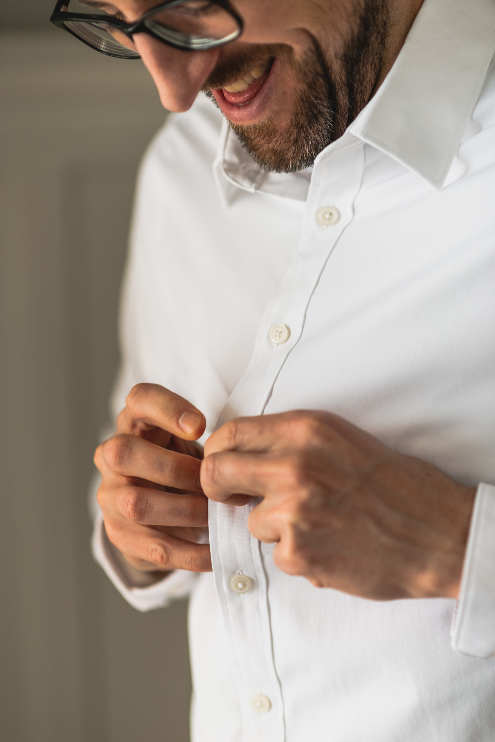 Groom buttoning shirt
