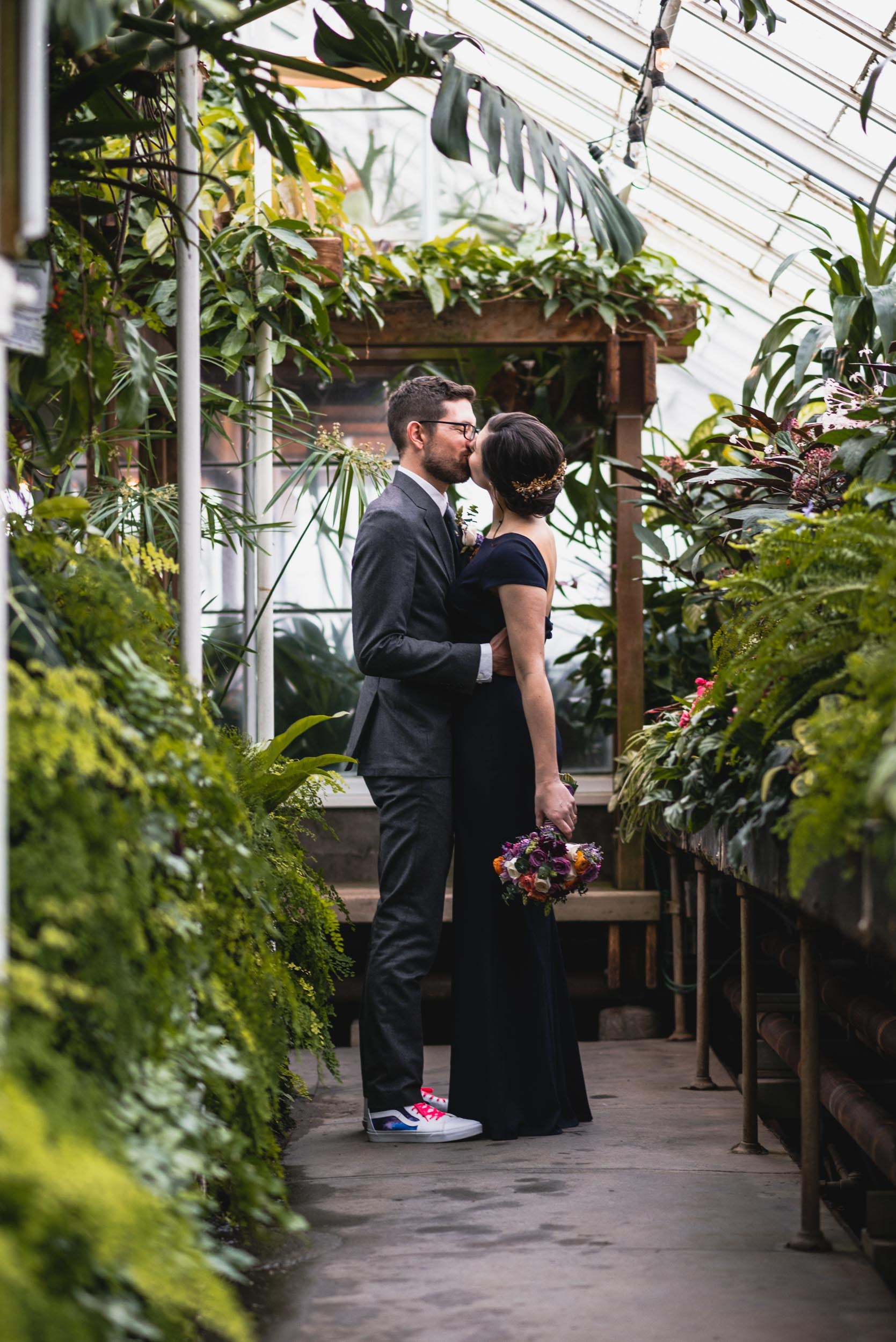 Bride and groom kiss among plants