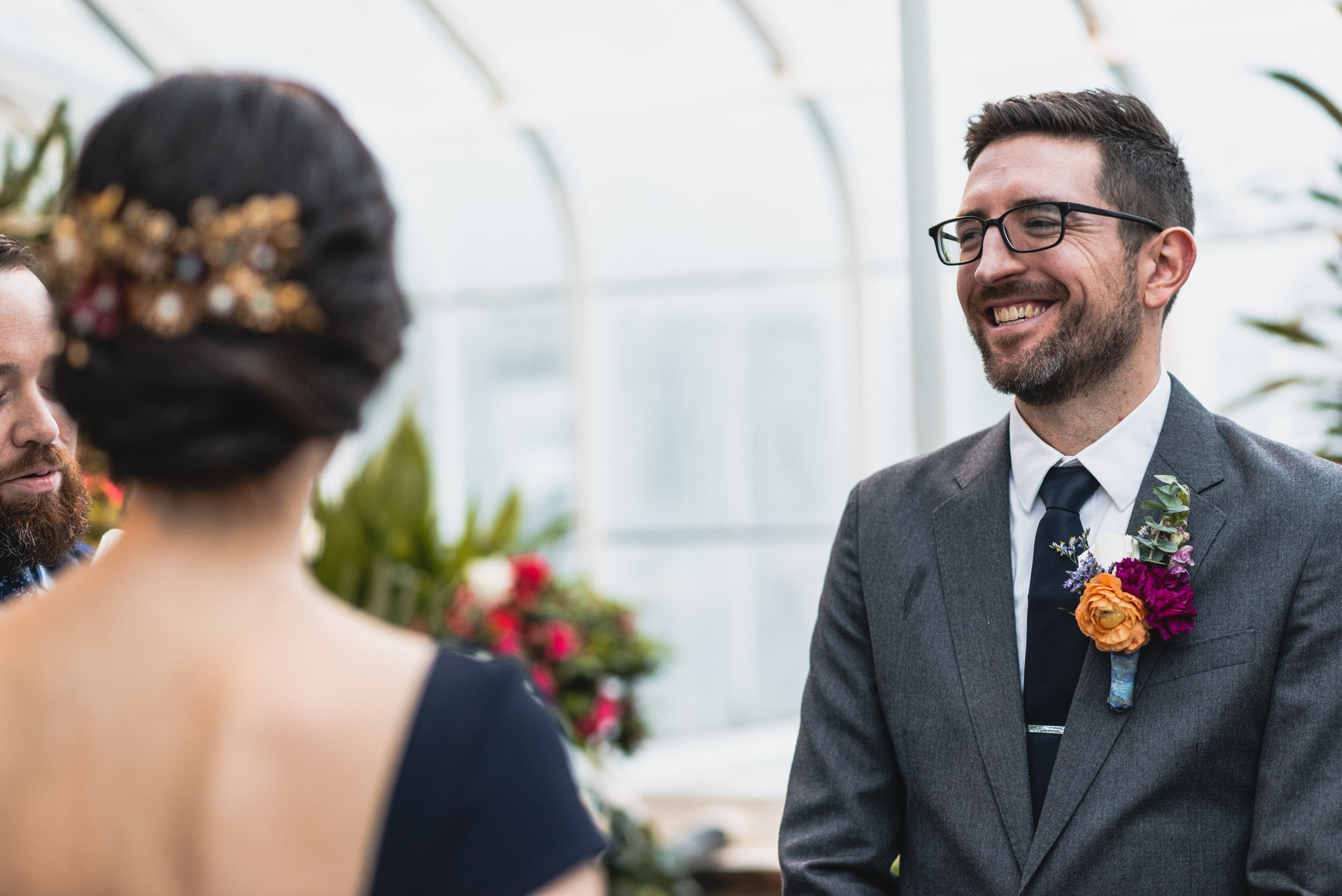 Groom smiles at Bride in conservatory