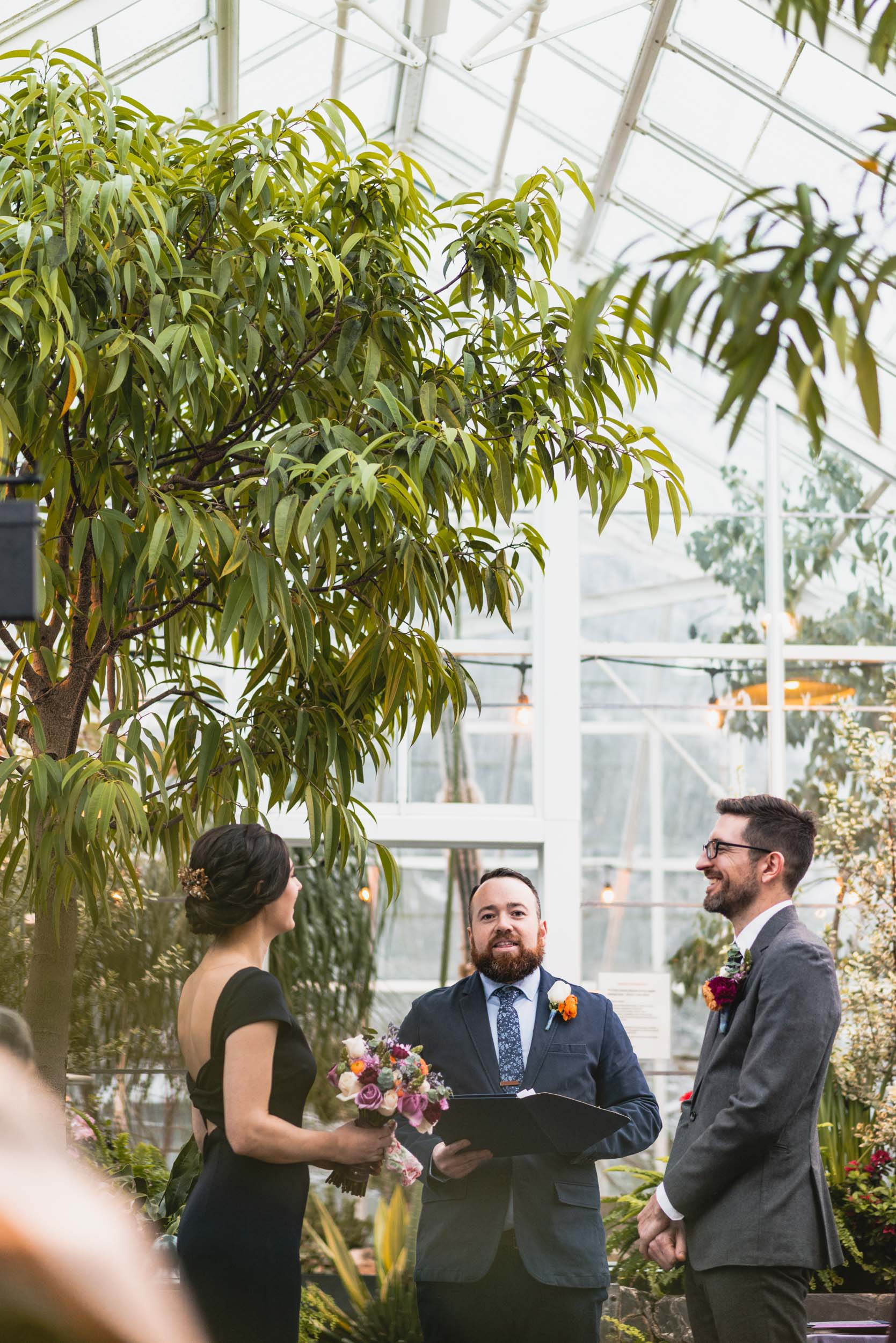 Groom, Bride and Officiant in conservatory