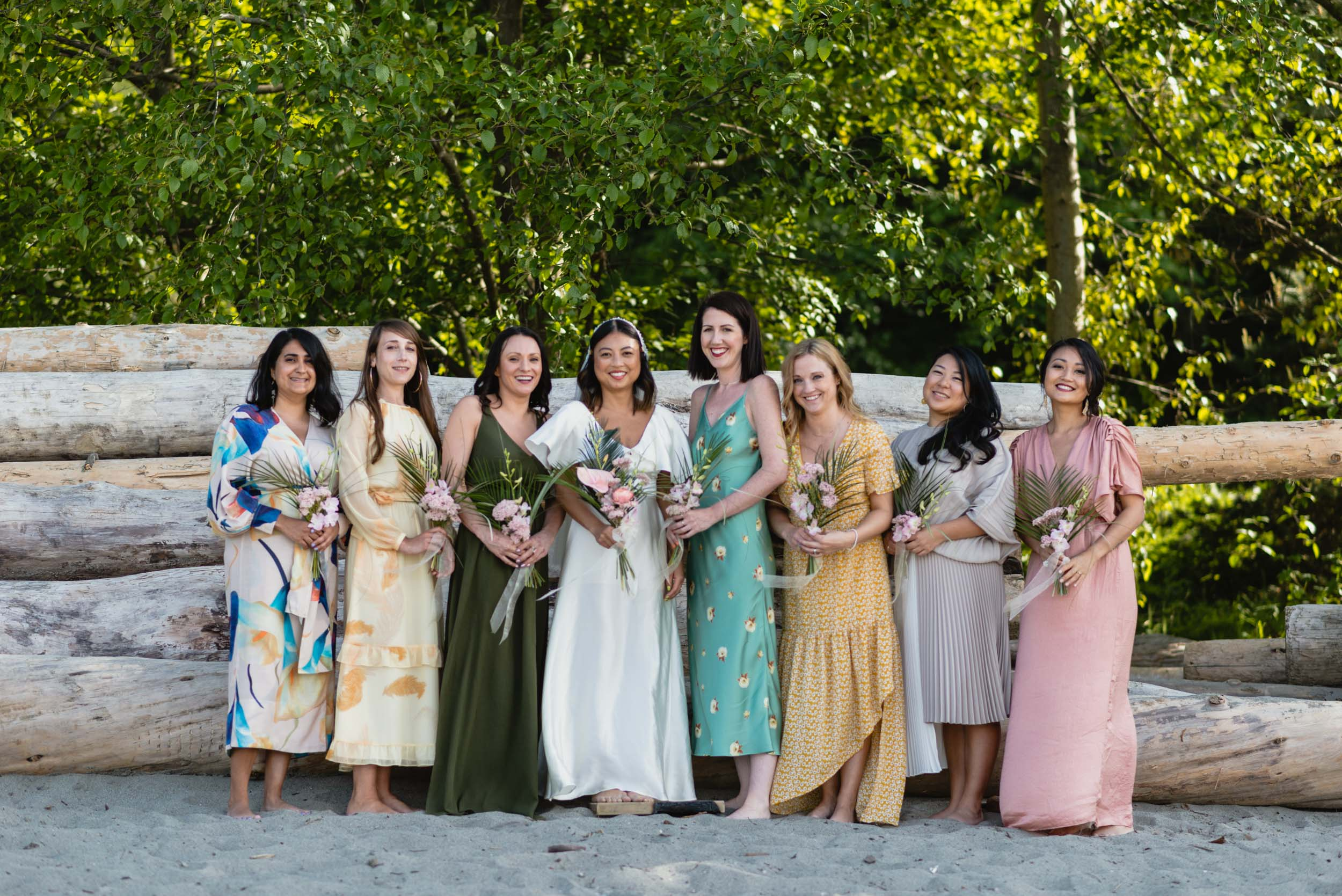Bride and bridesmaids at beach with logs