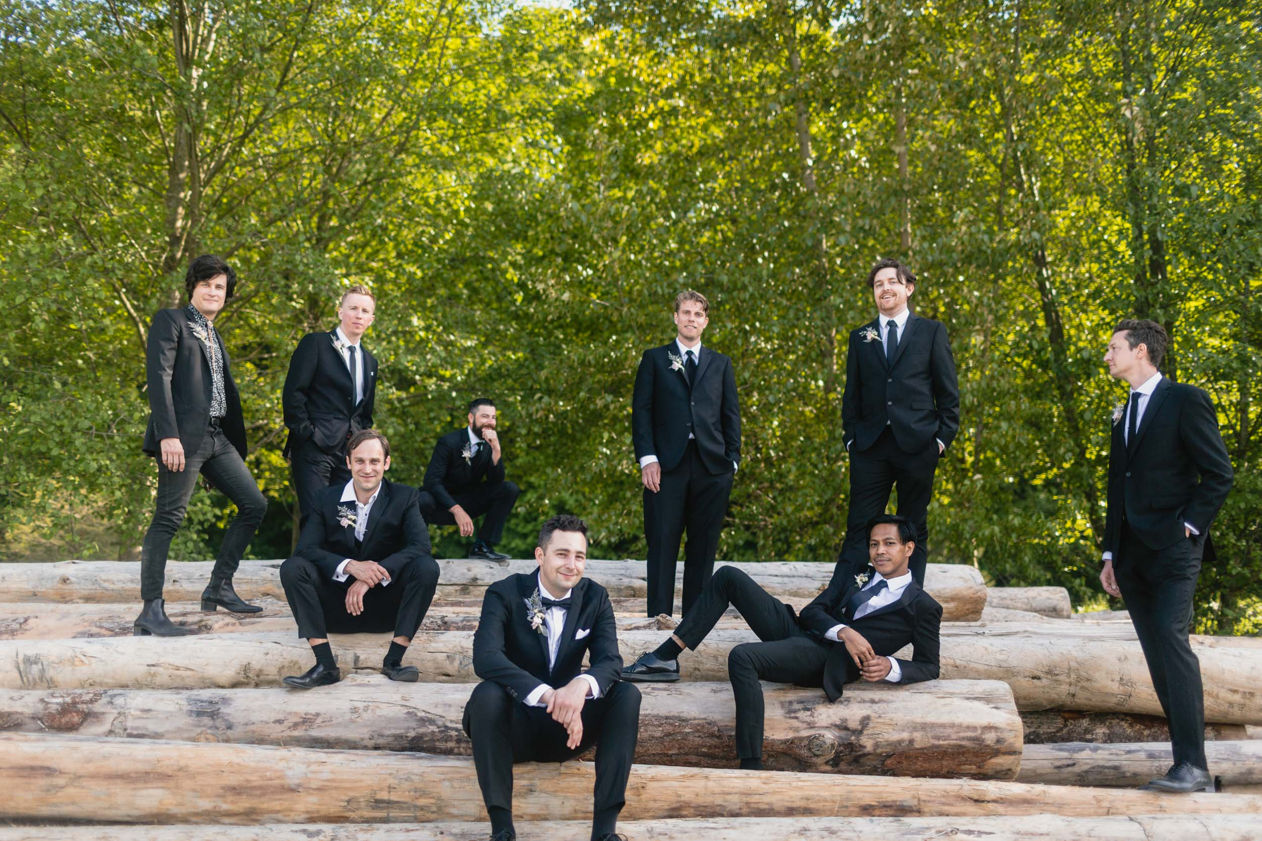 Groom and groomsmen at beach with logs