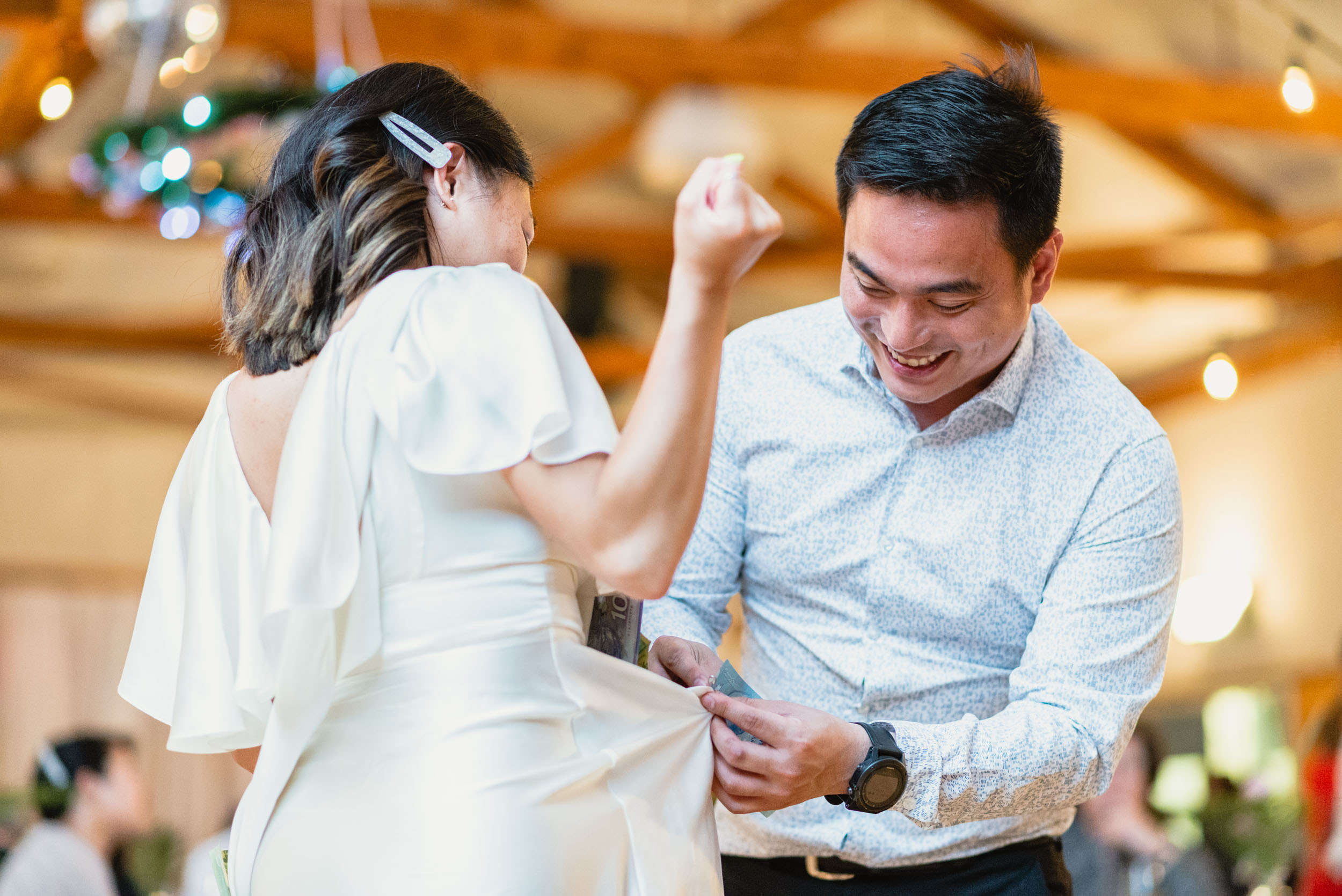 Guest pinning money on Bride