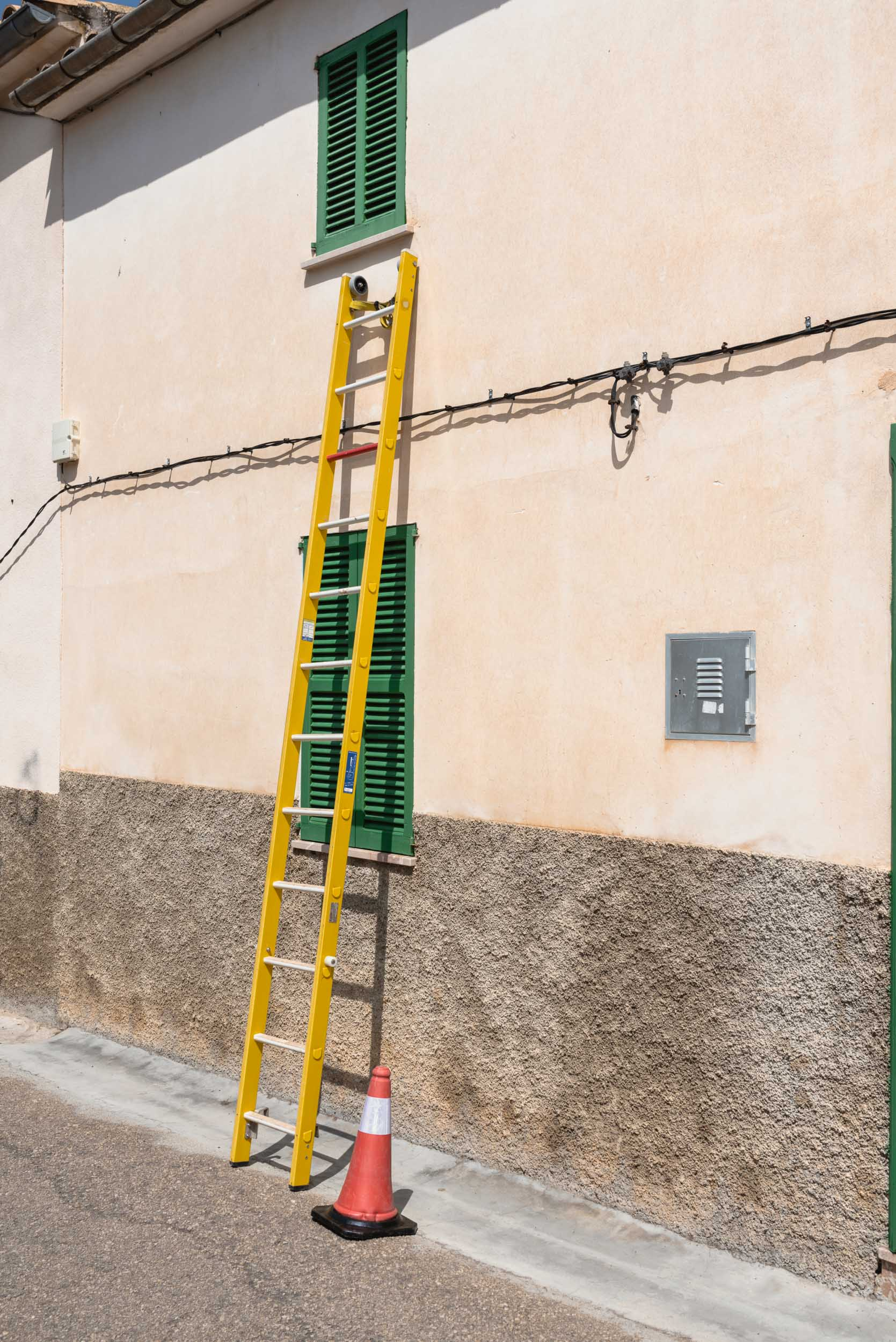 Yellow ladder on building in Sineu, Spain