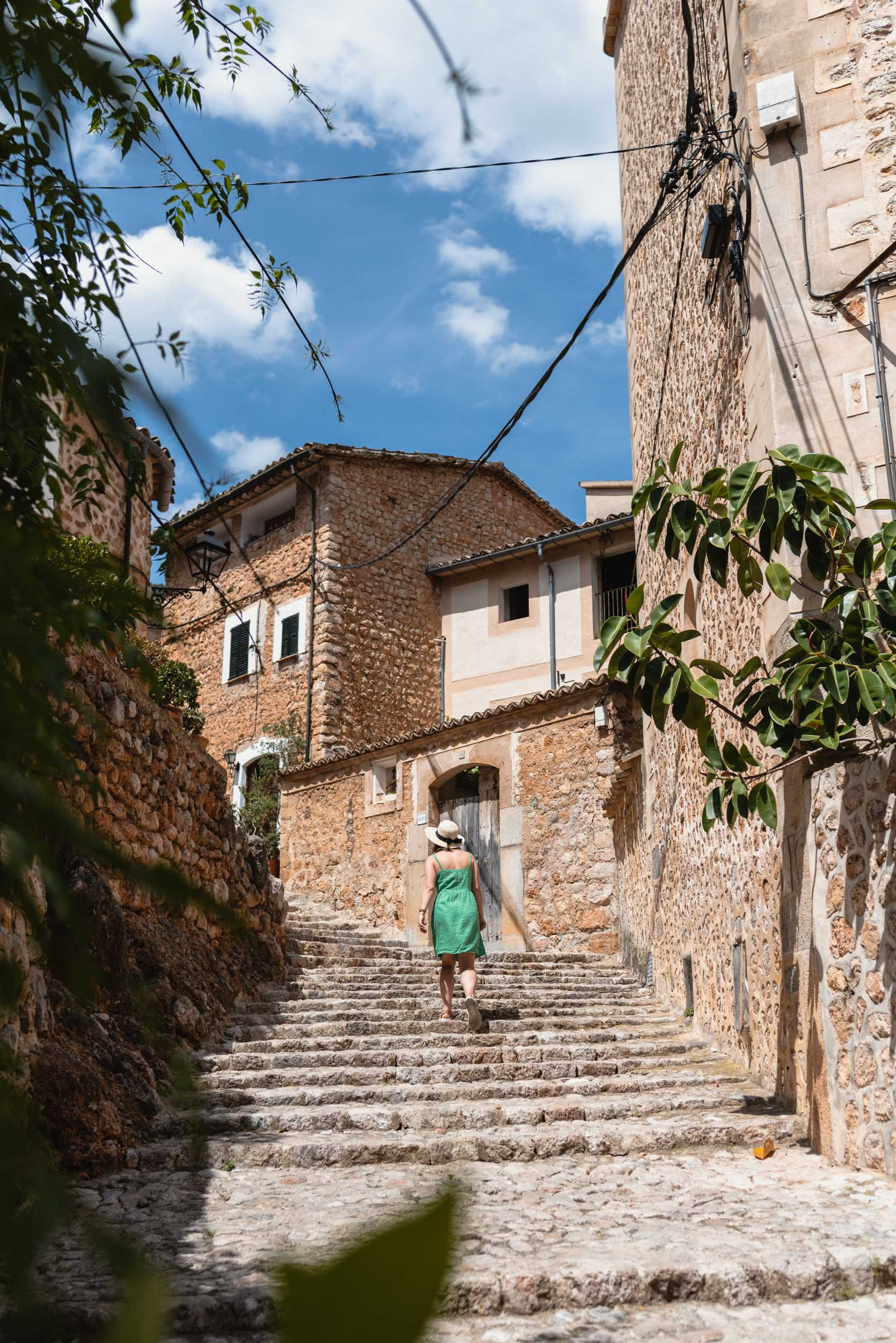 Woman in green dress walking through Fornalutx, Spain