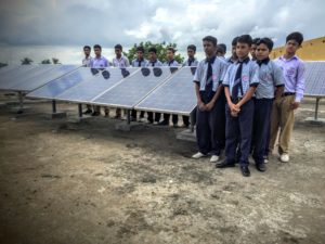 INDIAN SCHOOLBOYS STAND NEXT TO ONERGY'S MICRO-GRID SOLAR PANELS.