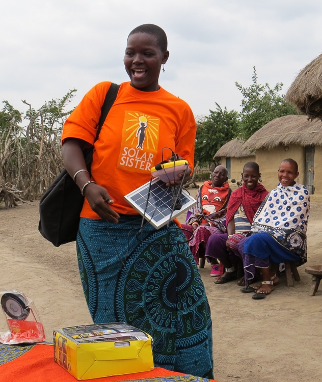 A SOLAR SISTER DEMONSTRATES HOW SHE ADVERTISES SOLAR SISTER LANTERNS AT MARKET DAY EVENTS, WHICH ARE LOCATED AN EIGHT-HOUR WALK AWAY FROM HER HOME IN THE MAASAI VILLAGE IN HANDENI (TANGA REGION)