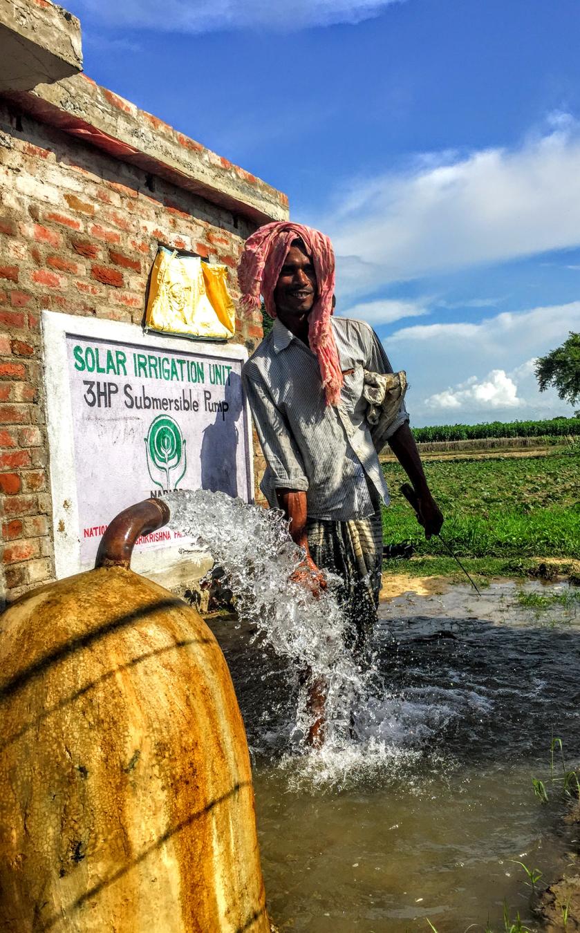 FARMERS IN NARANDI WITH A SOLAR POWERED WATER PUMP ON THEIR FARM.