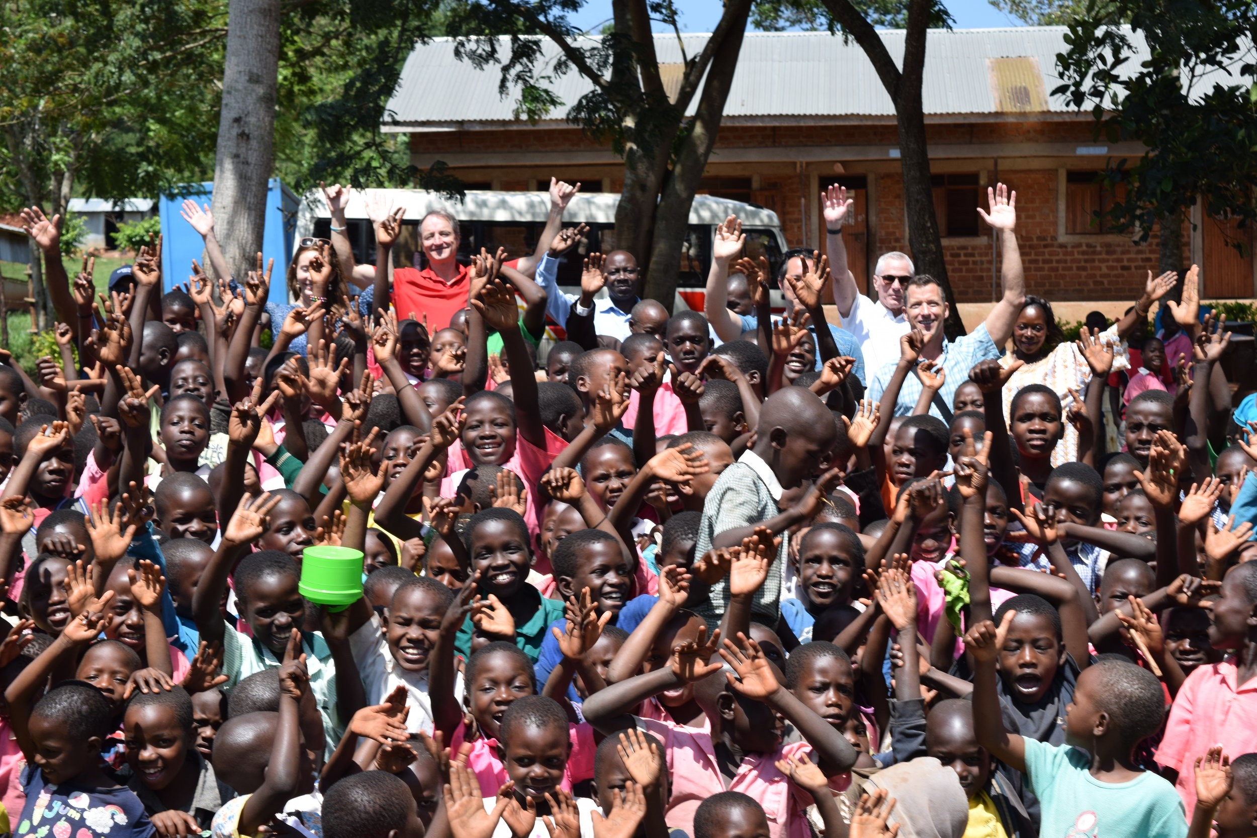 On International Women's Day, children and teachers from a school in Sentigi, Uganda greet participants on the immersion trip with Miller Center.