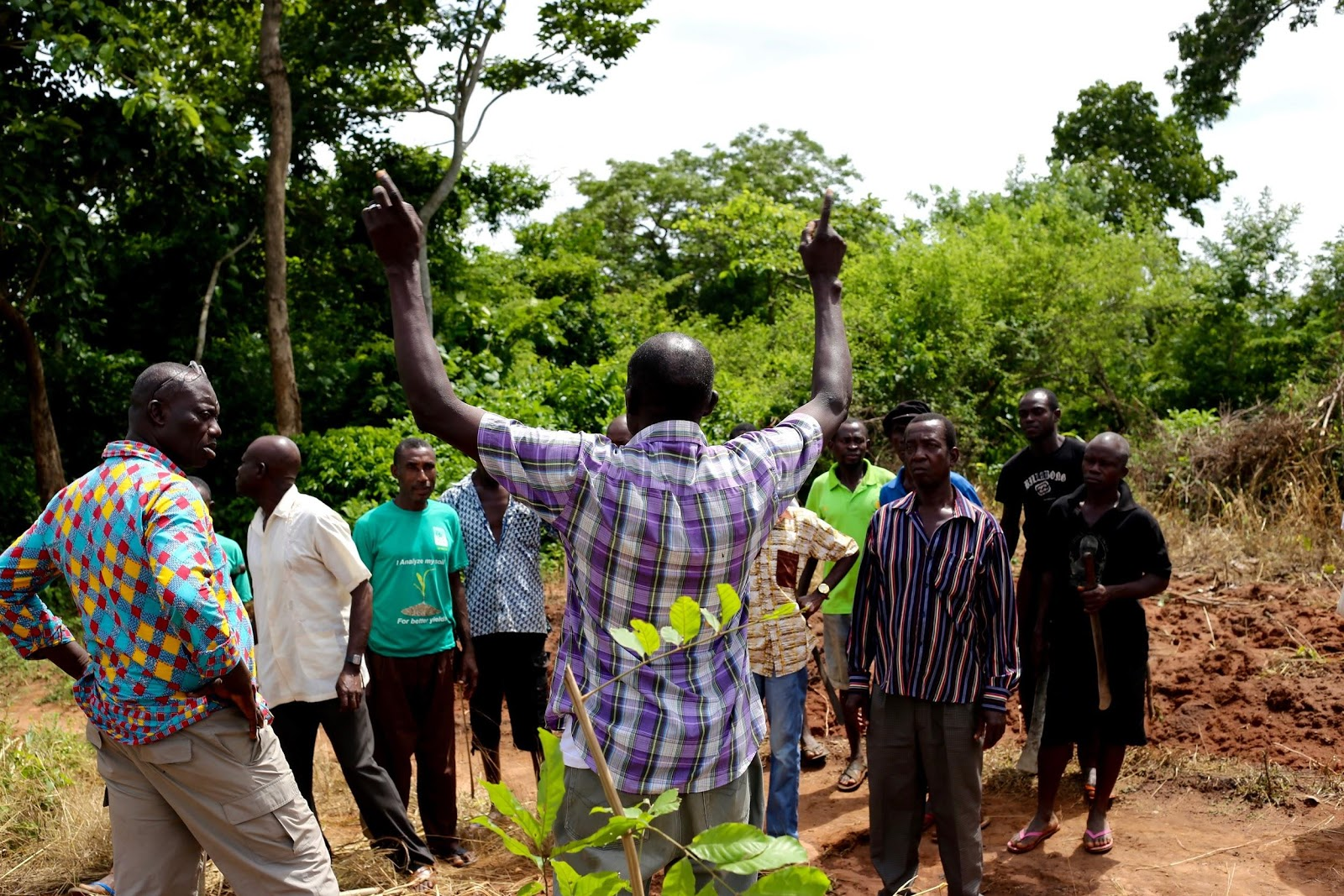 Mr. Nartey, a regional Manager for MoringaConnect, shows a crowd of field agents and farmers the best methods for planting moringa seeds.