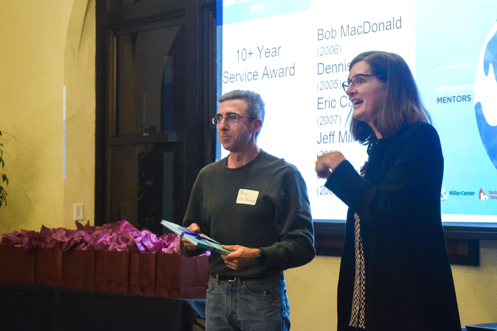 Bob MacDonald pictured receiving his gift, recognizing 10+ years of service as a mentor to Miller Center social entrepreneurs.