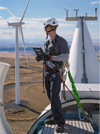 A wind turbine technician using a tablet interface for routine field repair & maintenance