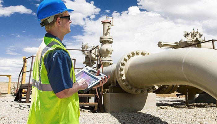 Oil pipeline and gas utility field service technician making use of a tablet app