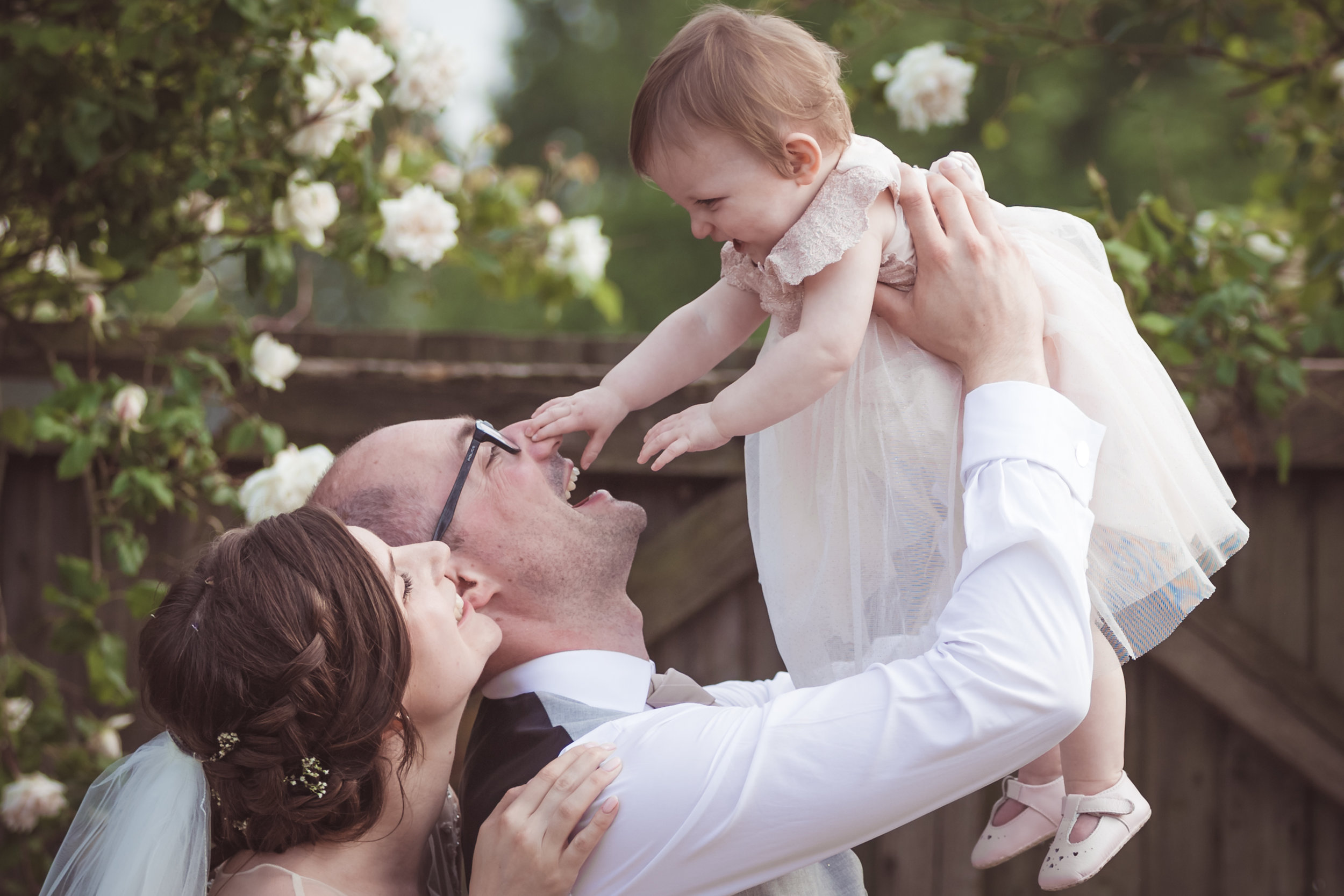 Dodford Manor bride and groom with child, close up, happy, laughing, roses, gate, natural wedding photogaphy, Best wedding photographers in Northamptonshire, natural, creative, Leicestershire, Rutland, Cambridgeshire, wedding, wedding photographers, wedding photography, Sara Mayer, Douglas Mayer, Fotovida Photography, excellent reviews, premium wedding photographers, premium service