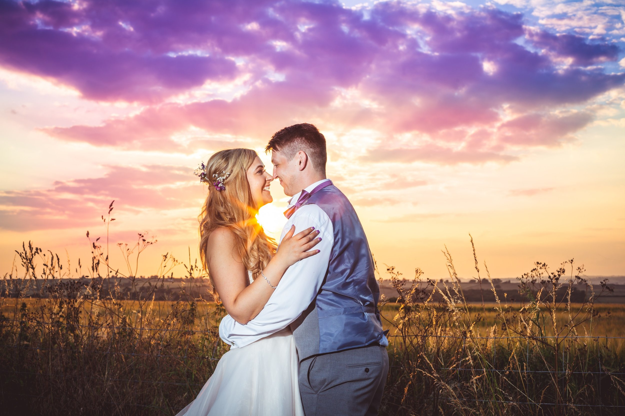 sunset over field behind bride and groom smiling, Best wedding photographers in Northamptonshire, natural, creative, Leicestershire, Rutland, Cambridgeshire, wedding, wedding photographers, wedding photography, Sara Mayer, Douglas Mayer, Fotovida Photography, excellent reviews, premium wedding photographers, premium service