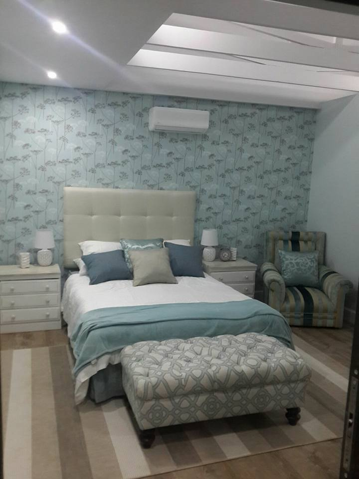 Here I reupholstered the ottoman & chair as well as repainted the bedside tables. Splurged on the fabric for ottoman and chair. The wallpaper is a beautiful feature in this tranquil room.
