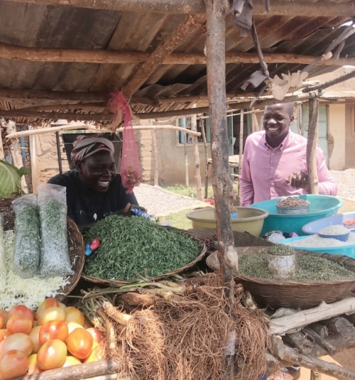 Wesley chatting with a Cherehani Africa client, a vegetable vendor in Lwak market in Siaya County