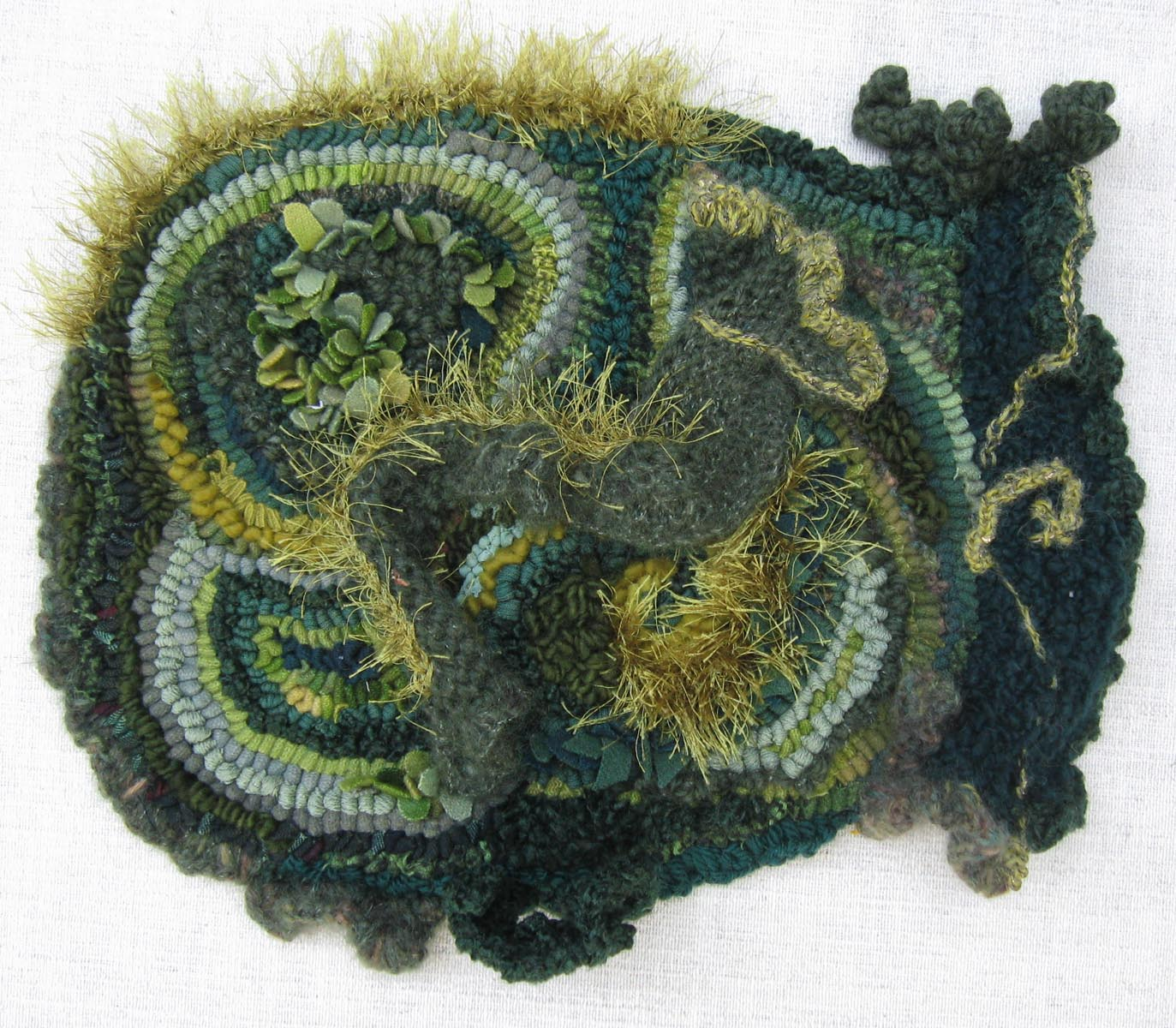 """Moss   2010, aprox 1.5"""" x 13"""" x 15"""", wool, cotton and mixed fiber in fabric and yarn; hand hooked, knit, crocheted and embroidered on Monk's cloth."""
