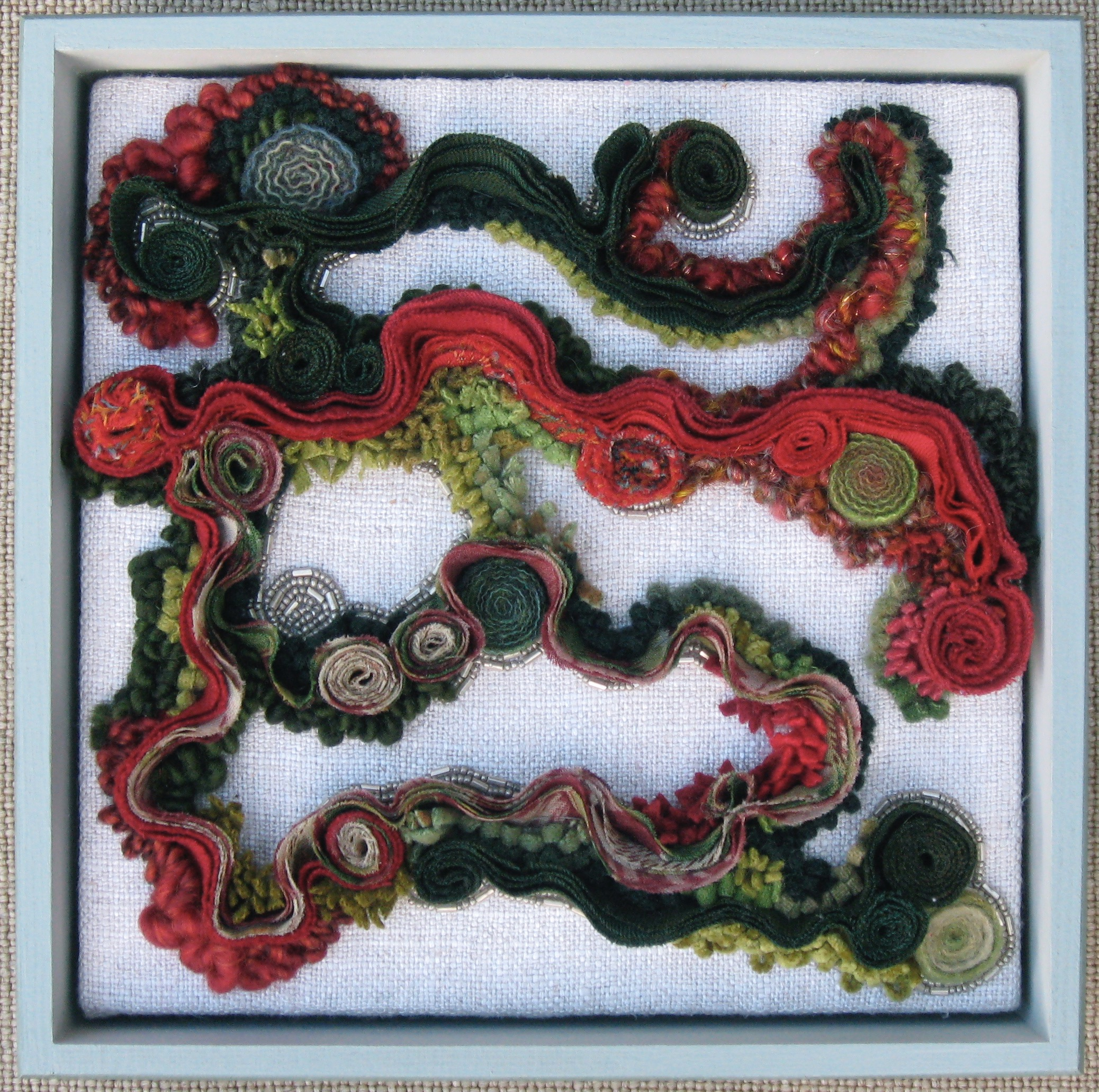 """Wandering   2011 9"""" x 9"""" x 3"""" Wool, antique paisley shawl, glass beads hand sewn, hand hooked, bias shirred and coiled."""