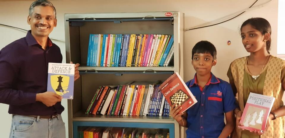 GM Ramesh shows off some of his Quality Chess books, with his star students GM Praggnanandhaa and WIM Vaishali (photo courtesy of GM Ramesh)