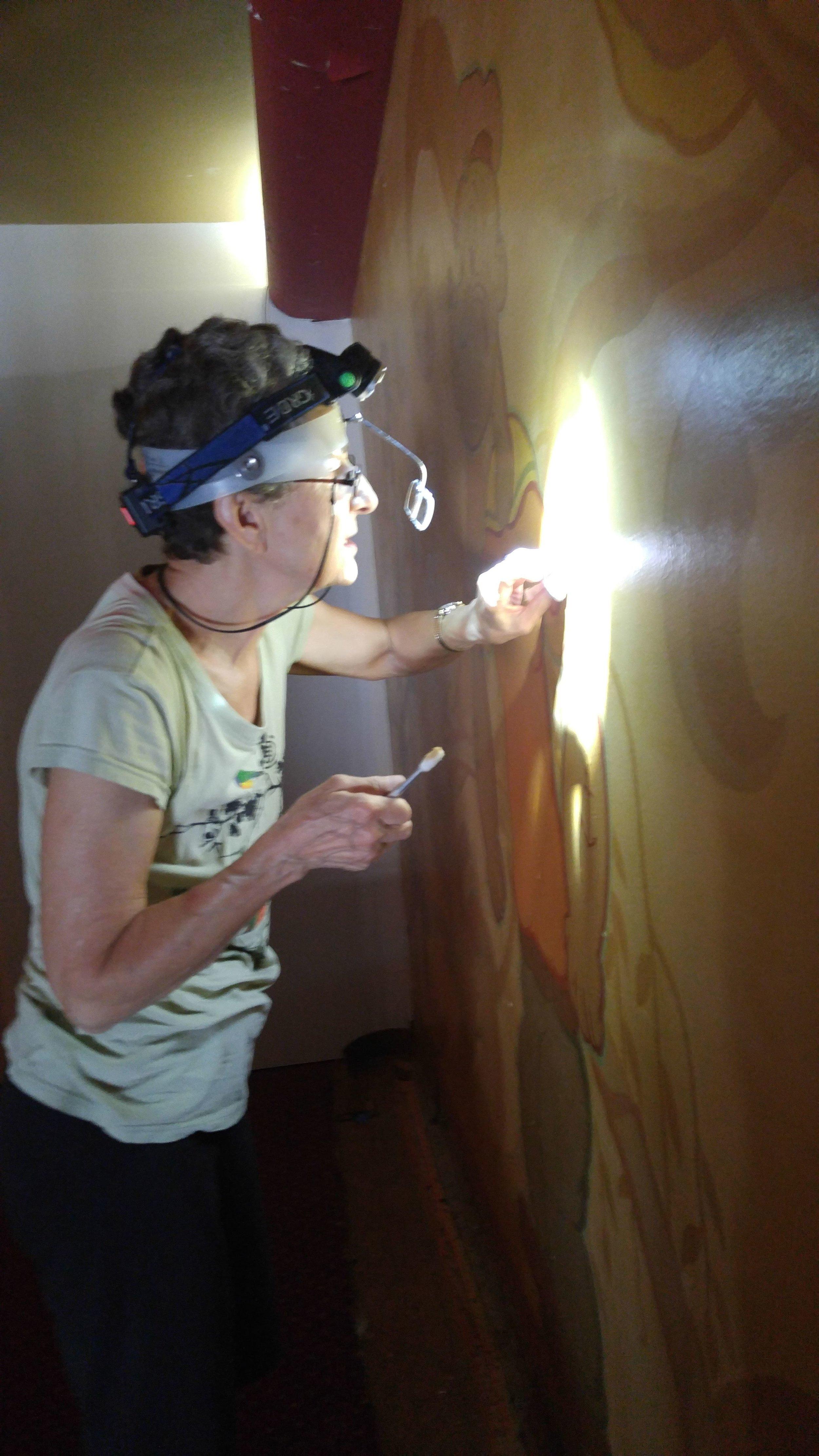 Decorative arts conservator Stashka Star examines the murals.