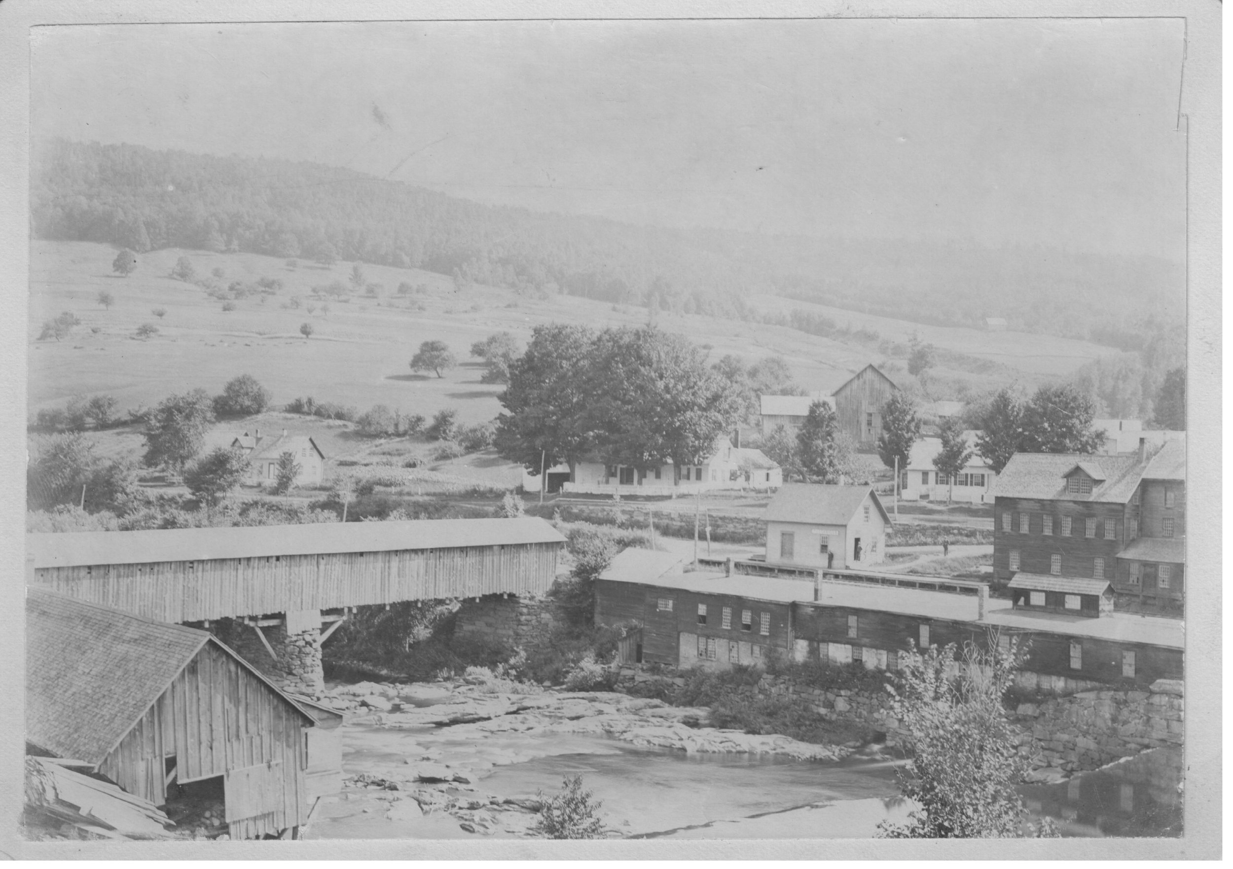 The Center of Taftsville - A view of the bridge, mills, railroad depot, houses and other buildings.
