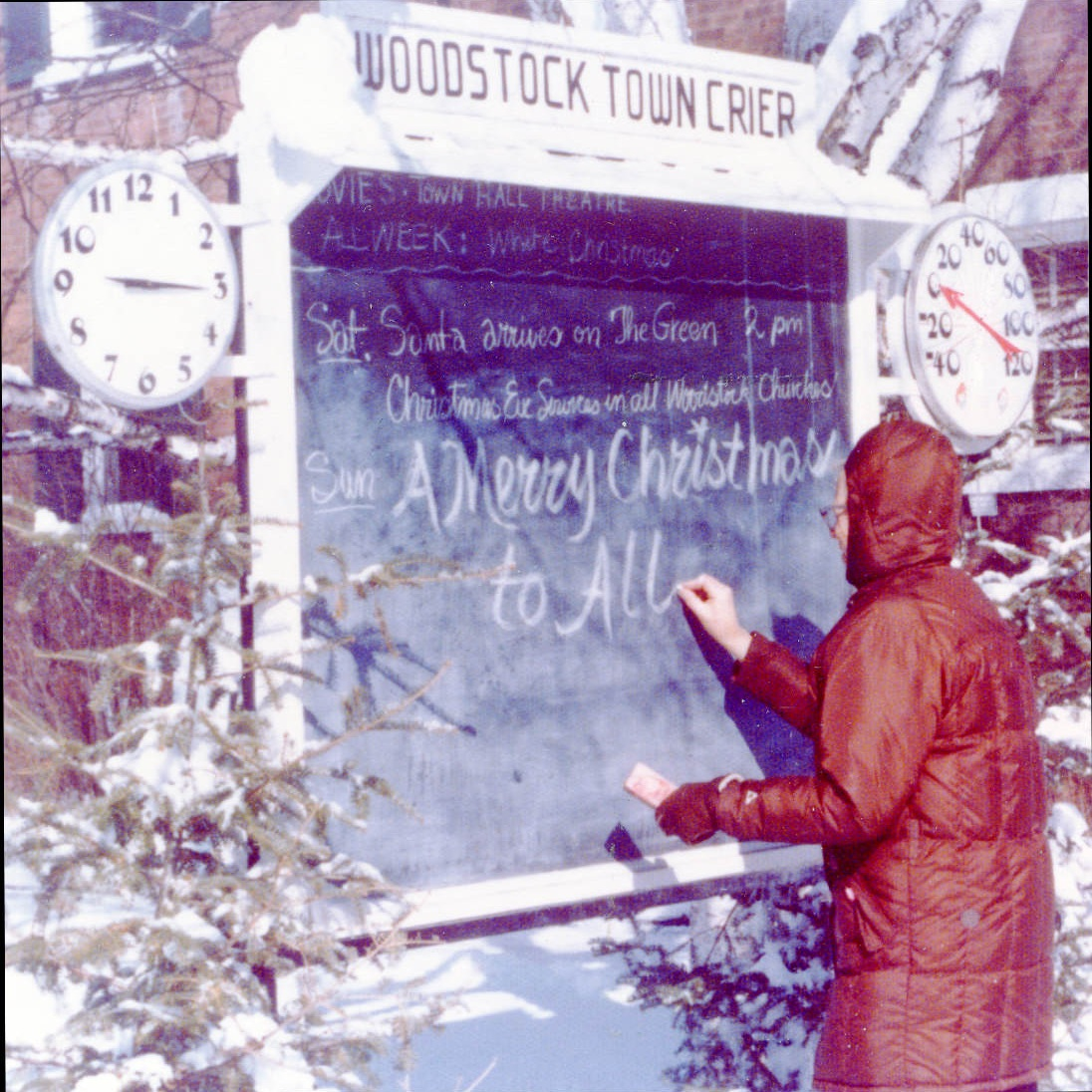 """Frank writing a holiday message on the """"Woodstock Town Crier."""" Frank maintained this chalkboard year round, regardless of the temperature. Notice, the thermometer to the right of the board reads """"0"""" degrees."""