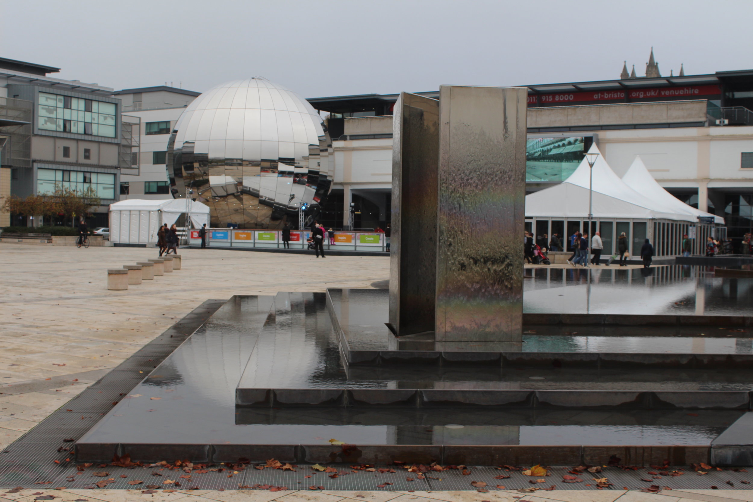 A water fountain disguised as steps, in front of the Planetarium (mirrored ball) and an ice rin