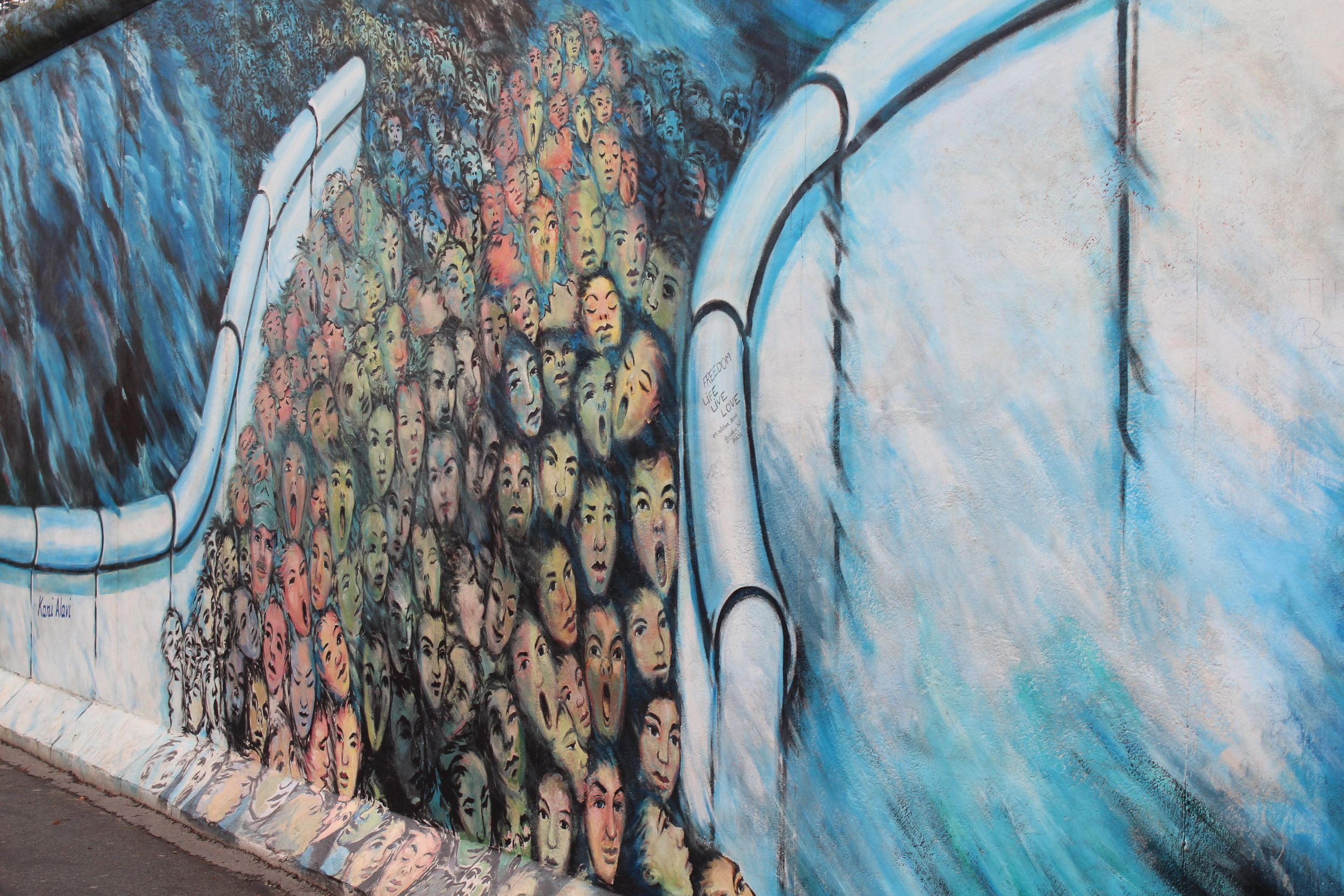 """Kani Alavi, who moved from Iran to West Berlinin 1980, used to live four metres away from the wall, next to Checkpoint Charlie. This painting, """"Es geschah im November"""", shows thousands of insecure and sad faces of East Berliner's crossing over to the west when the wall came down. He often speaks out about his surprise when he looked closer at the expressions from East Berliners and found fear rather than excitement."""