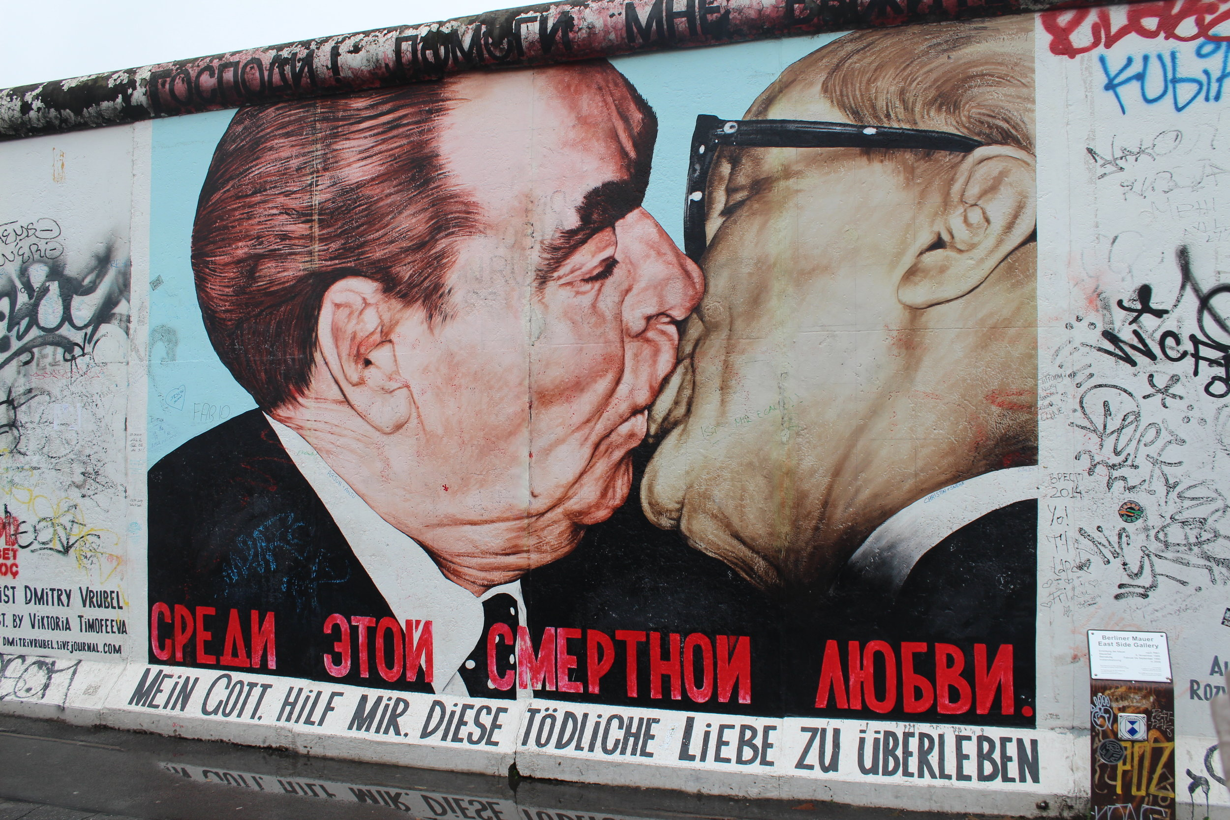 """Here it is. The famous painting of two men kissing. The painting that people crowded around with their selfie sticks, ipads, phones and DSLRs. Yes, lots of people kissed in front of it - we saw three couples take kissing photos in the space of a minute. And yes, it is even more amazing in the """"flesh""""/on the wall.  The painting, """"Mein Gott hilf mir, diese tödliche Liebe zu überleben"""" (translated to """"My God, help me to survive this deadly love"""" in English) was painted by Dmitri Wrubel. It depicts an iconic photograph of Leonid Brezhnev and Erich Honecker in a socialist fraternal kiss, taken by Régis Bossu in East Berlin on October 7, 1979."""